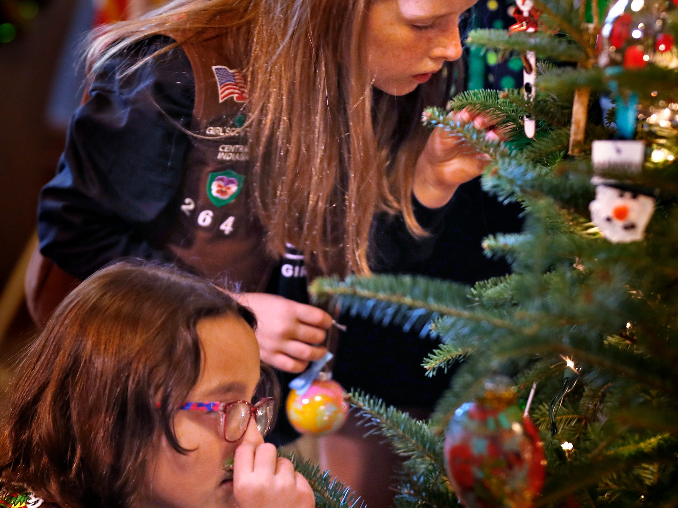 Brownies Josie Pardo, lower, and Vivian Bruno sniff the tree to see if it is real, as they join Lieutenant Governor Suzanne Crouch to decorate her Indiana Statehouse tree for the holidays, Wednesday, Dec. 5, 2018.  They used ornaments created by Girl Scouts from across Central Indiana for the tree.