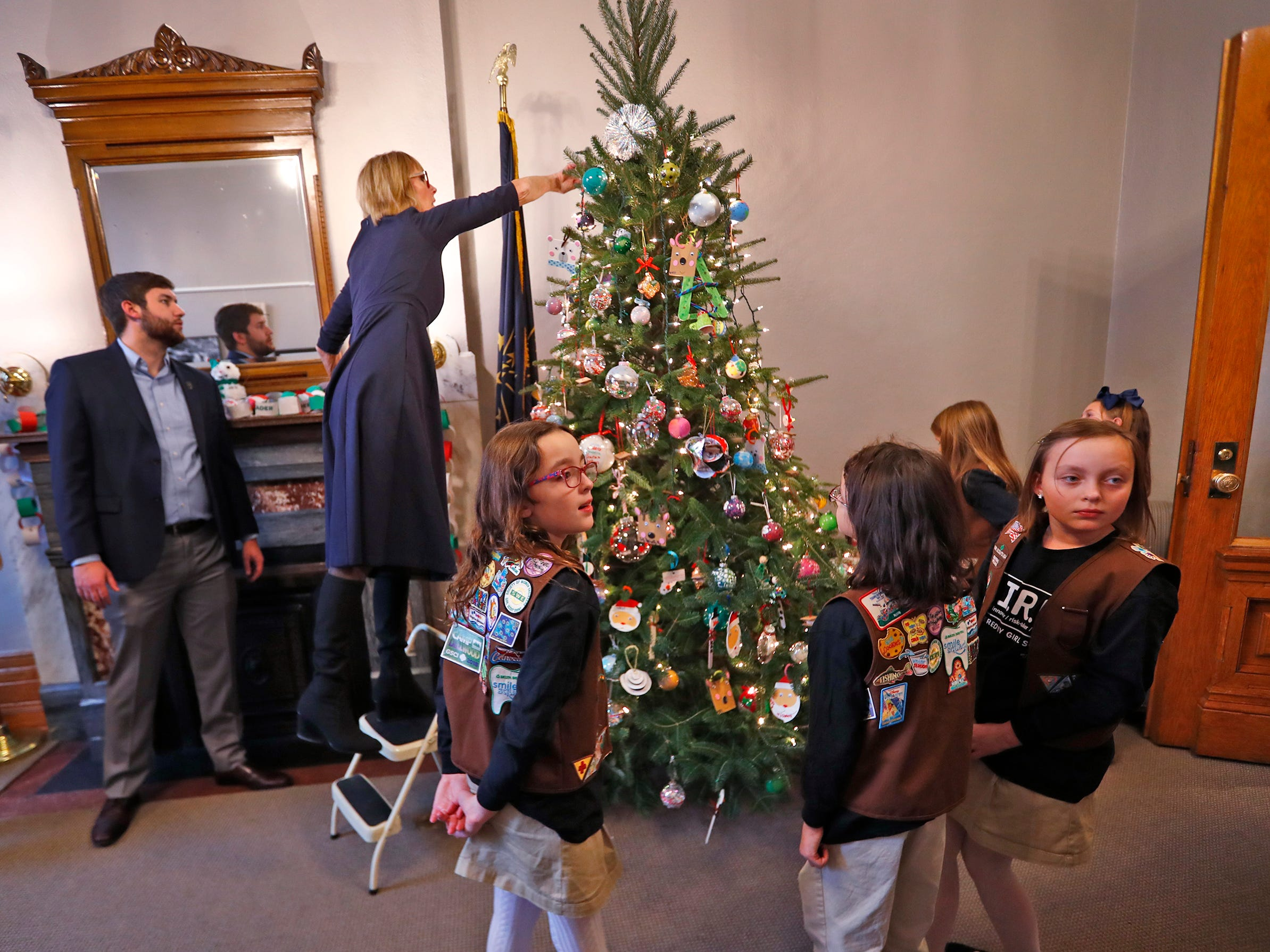 Lieutenant Governor Suzanne Crouch reaches to put a finishing touch on her Statehouse office tree, as she is joined by Girl Scouts to decorate her tree for the holidays, Wednesday, Dec. 5, 2018.  They used ornaments created by Girl Scouts from across Central Indiana for the tree.