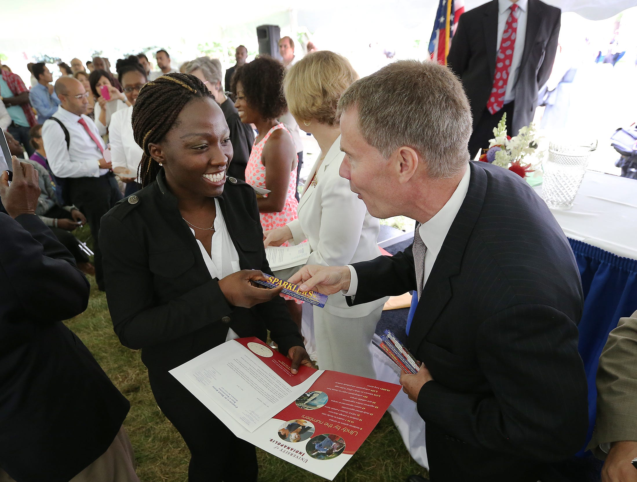 A total of 101 people from numerous countries were sworn in as US citizens during a Naturalization ceremony Thursday, July 3, 2014, morning at the President Benjamin Harrison home. Here Ademofe Adefemiwa is handed a box of sparklers by US Attorney Joseph Hogsett,right, following the ceremony.