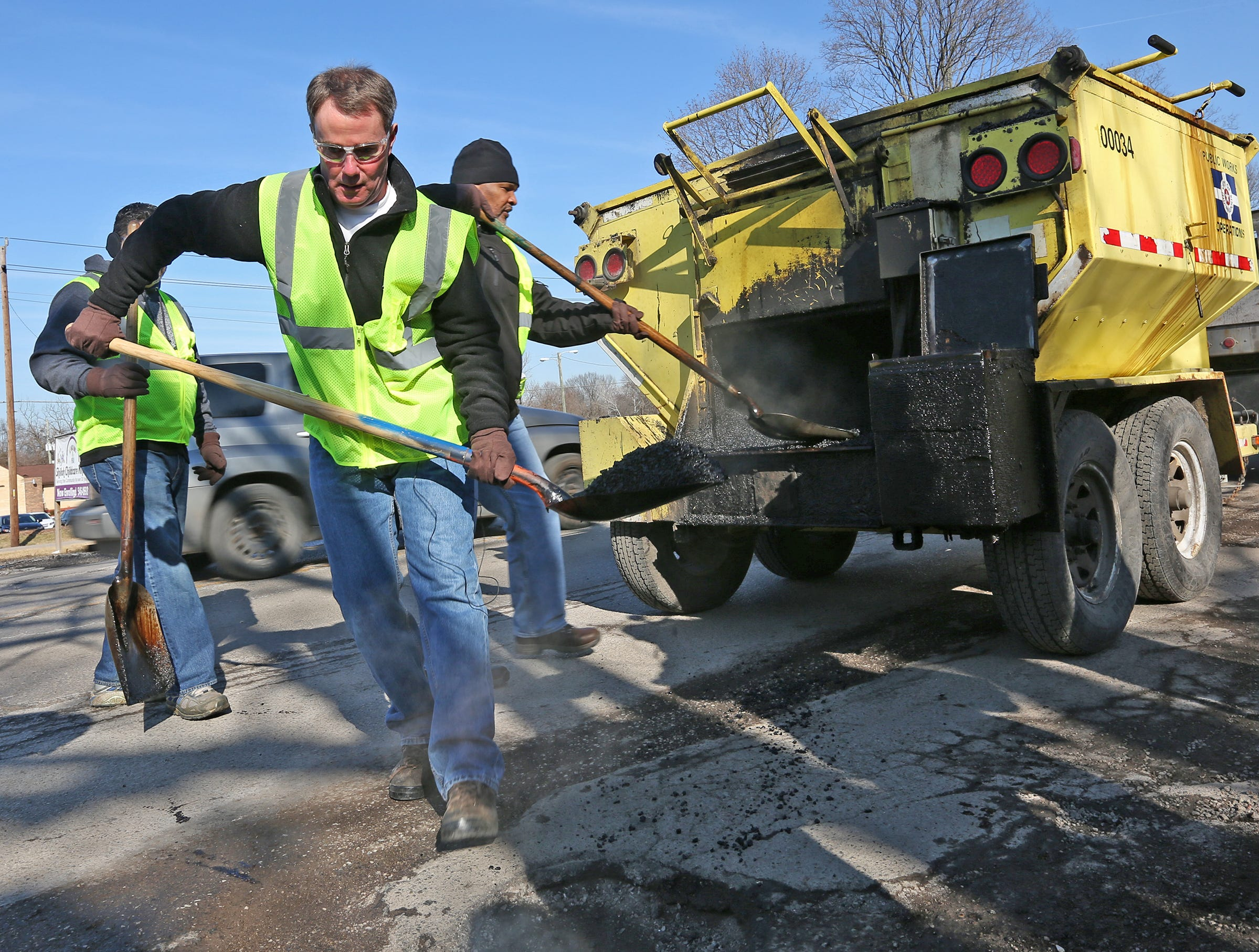 Mayor Joe Hogsett pitches in to fill pot holes on the first day of a 4-day pothole blitz, joining a crew from the Indianapolis Department of Public Works (DPW) near the intersection of 38th St. and Forest Manor Ave., Monday, Jan. 30, 2018.  DPW crews are using hot mix, an asphalt mix that lasts longer and adheres better.