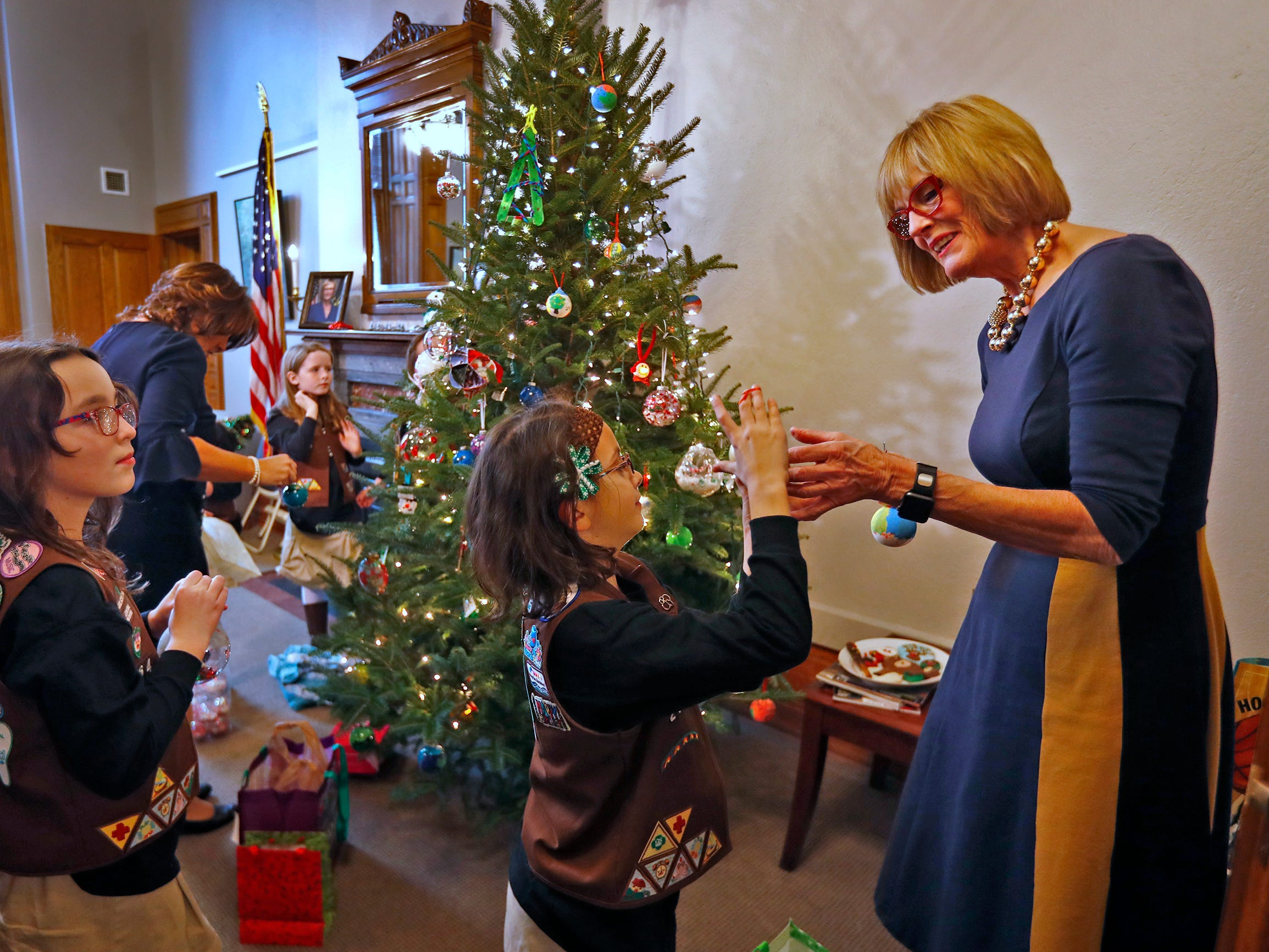 Josie Pardo, left, Ivy Lara, center, and other Brownies join Lieutenant Governor Suzanne Crouch to decorate her Indiana Statehouse tree for the holidays, Wednesday, Dec. 5, 2018.  They used ornaments created by Girl Scouts from across Central Indiana for the tree.
