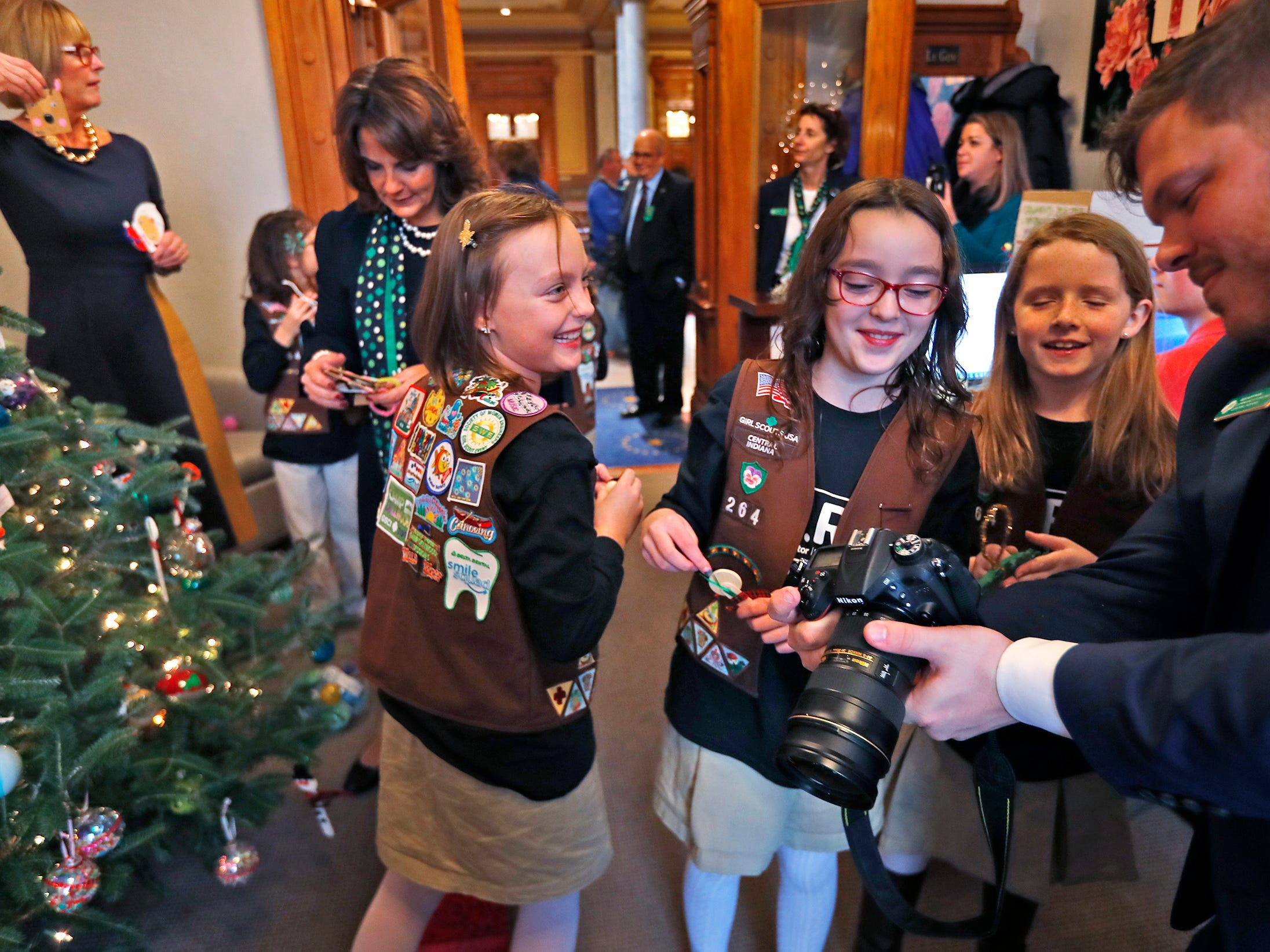 Brownies laugh as they see a photo of themselves as they join Lieutenant Governor Suzanne Crouch to decorate her Indiana Statehouse tree for the holidays, Wednesday, Dec. 5, 2018.  They used ornaments created by Girl Scouts from across Central Indiana for the tree.