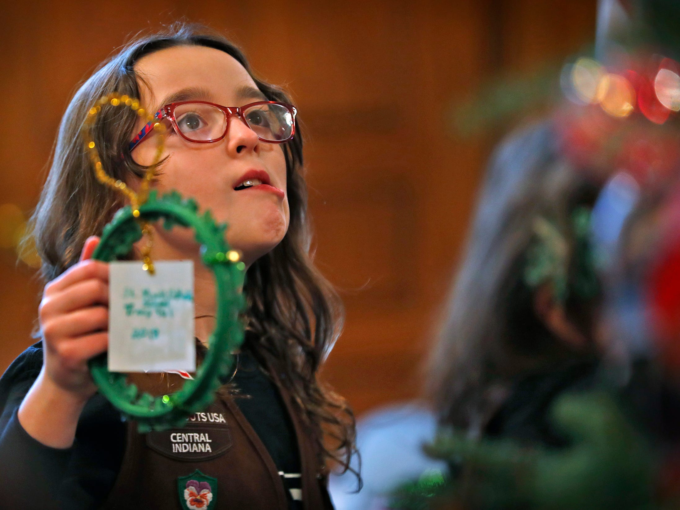 Josie Pardo looks for a spot to add an ornament as she and other Brownies join Lieutenant Governor Suzanne Crouch to decorate her Indiana Statehouse tree for the holidays, Wednesday, Dec. 5, 2018.  They used ornaments created by Girl Scouts from across Central Indiana for the tree.
