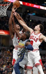 Indiana Pacers guard Aaron Holiday (3) fights for a rebound wigth Chicago Bulls guard Zach LaVine (8) and Wendell Carter Jr. (34) in the first half of their game at Bankers Life Fieldhouse on Tuesday, Dec. 4, 2018.