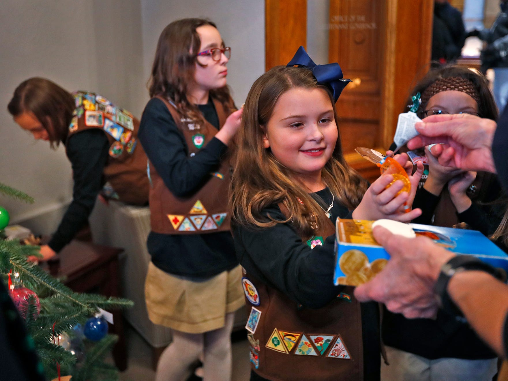 Katie Callahan, center, and other Brownies receive Hanukkah gold chocolate coins from Lieutenant Governor Suzanne Crouch after they helped her decorate her Statehouse tree for the holidays, Wednesday, Dec. 5, 2018.  They used ornaments created by Girl Scouts from across Central Indiana for the tree.