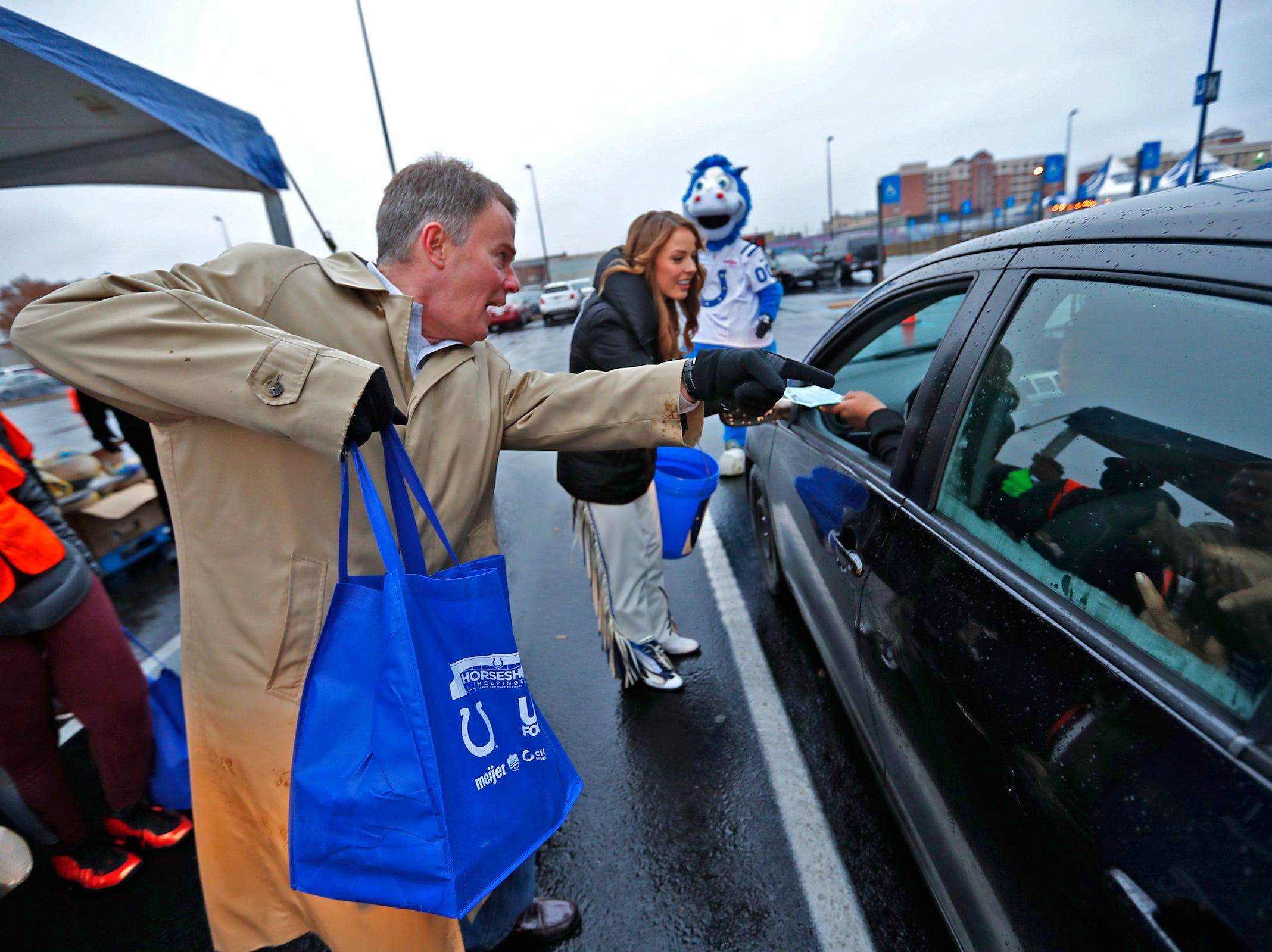 Mayor Joe Hogsett helps to distribute Thanksgiving meals to families at Lucas Oil Stadium, Monday, Nov. 19, 2018.