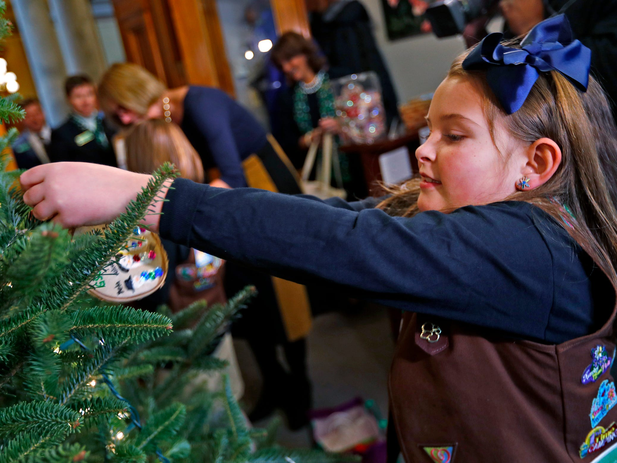 Katie Callahan reaches to hang an ornament, as she joins other Brownies and Lieutenant Governor Suzanne Crouch to decorate Crouch's Statehouse tree for the holidays, Wednesday, Dec. 5, 2018.  They used ornaments created by Girl Scouts from across Central Indiana for the tree.