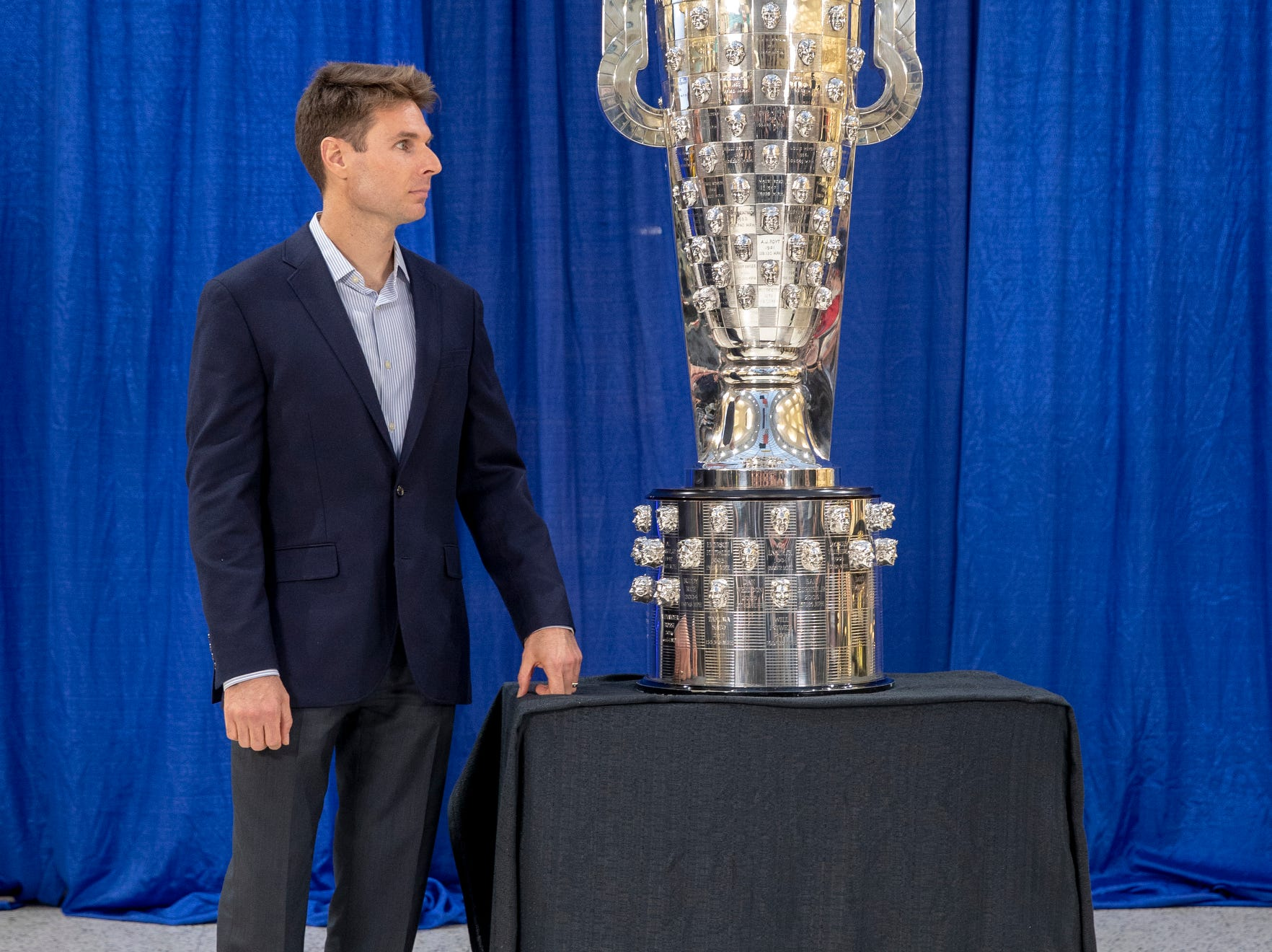 Will Power poses for photographers' cameras after his likeness was unveiled on the BorgWarner trophy, Indianapolis Motor Speedway, Wednesday, Dec. 5, 2018. Power is an Australian driver with Team Penske, and is the 105th face on the trophy.
