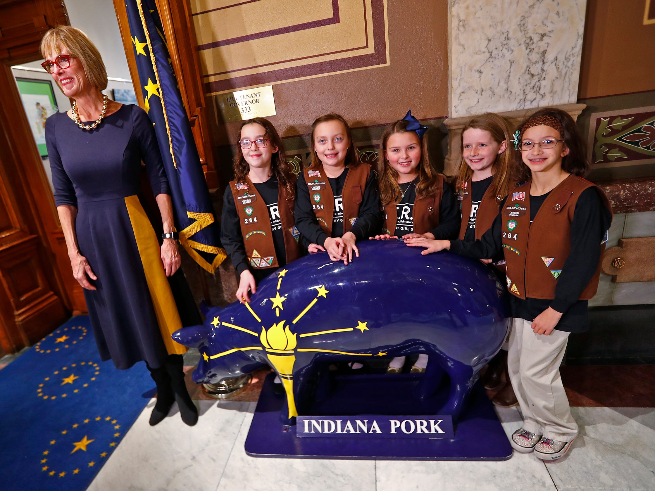Lieutenant Governor Suzanne Crouch, left, poses with Brownies, from left, Josie Pardo, Colette Pardo, Katie Callahan, Vivian Bruno, Ivy Lara and the famous Indiana Pork statue outside her office at the Indiana Statehouse, before they gather to decorate her office tree for the holidays, Wednesday, Dec. 5, 2018.  They used ornaments created by Girl Scouts from across Central Indiana for the tree.