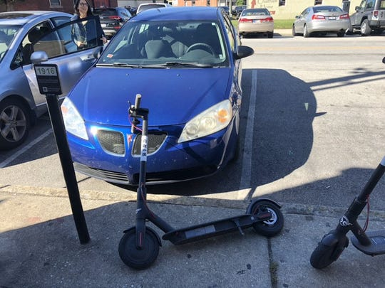 A Bird scooter sits on the hood of Matthew Kawiecki's 2007 Pontiac G6 as it's parked on Oct. 28, 2018, on Mass Ave. The scooter blew over in the wind, causing more than $400 in damage to the car.