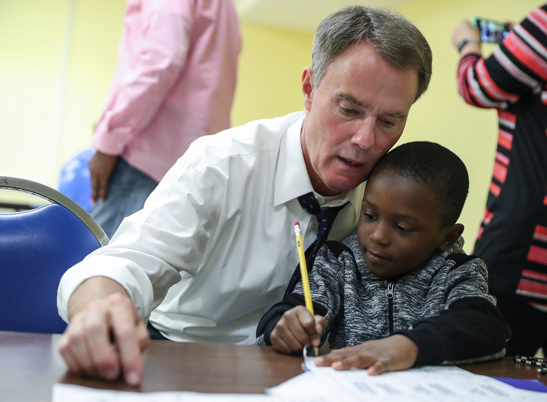Indianapolis Mayor Joe Hogsett stop to help Demerius Frierson, 6, with math homework while touring the Martin Luther King Community Center in Indianapolis, Tuesday, Sept. 11, 2018. Frierson participates in the Read to Lead after-school program.