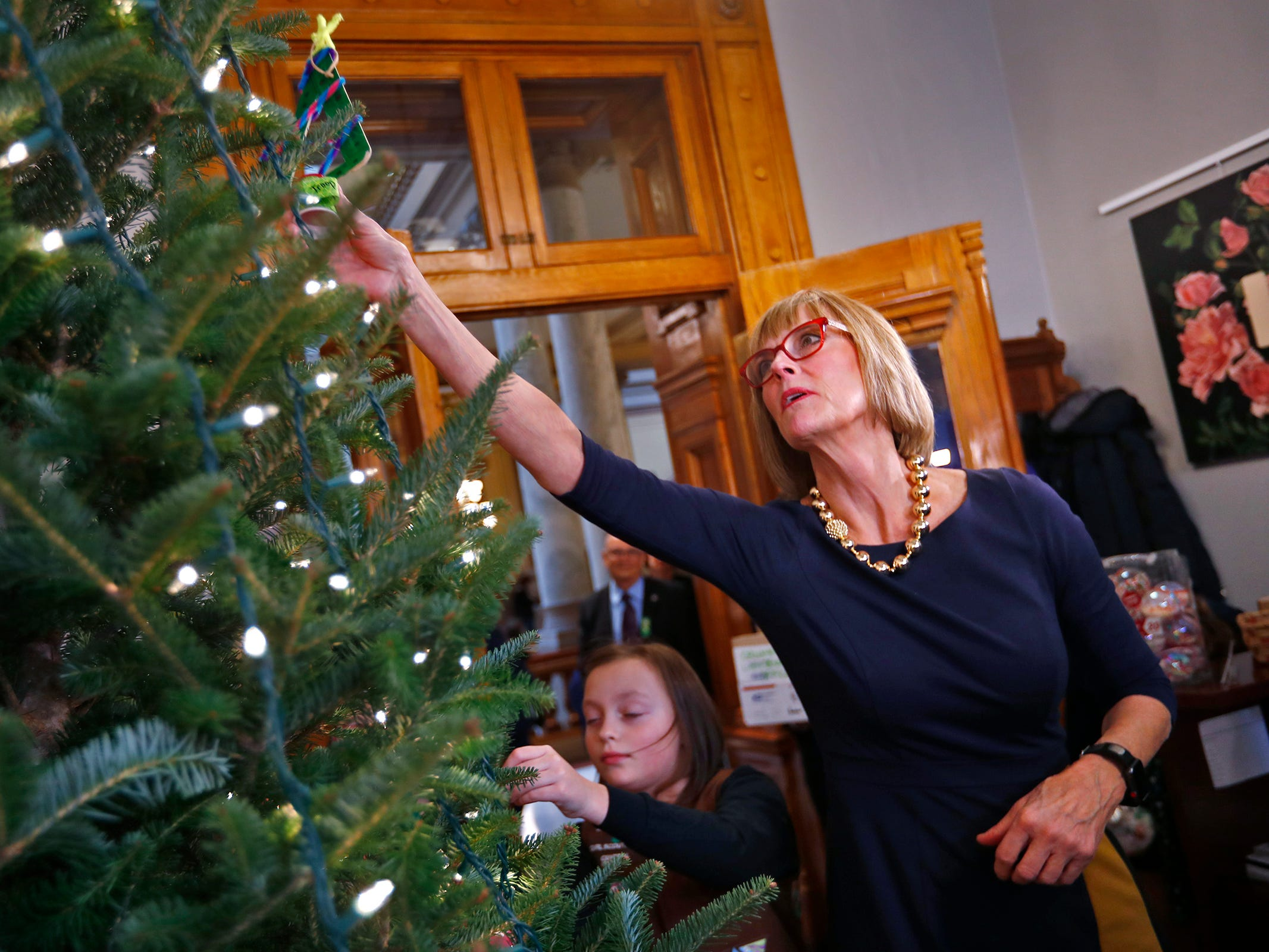 Colette Pardo, left, and other Brownies join Lieutenant Governor Suzanne Crouch, right, to decorate her Indiana Statehouse tree for the holidays, Wednesday, Dec. 5, 2018.  They used ornaments created by Girl Scouts from across Central Indiana for the tree.