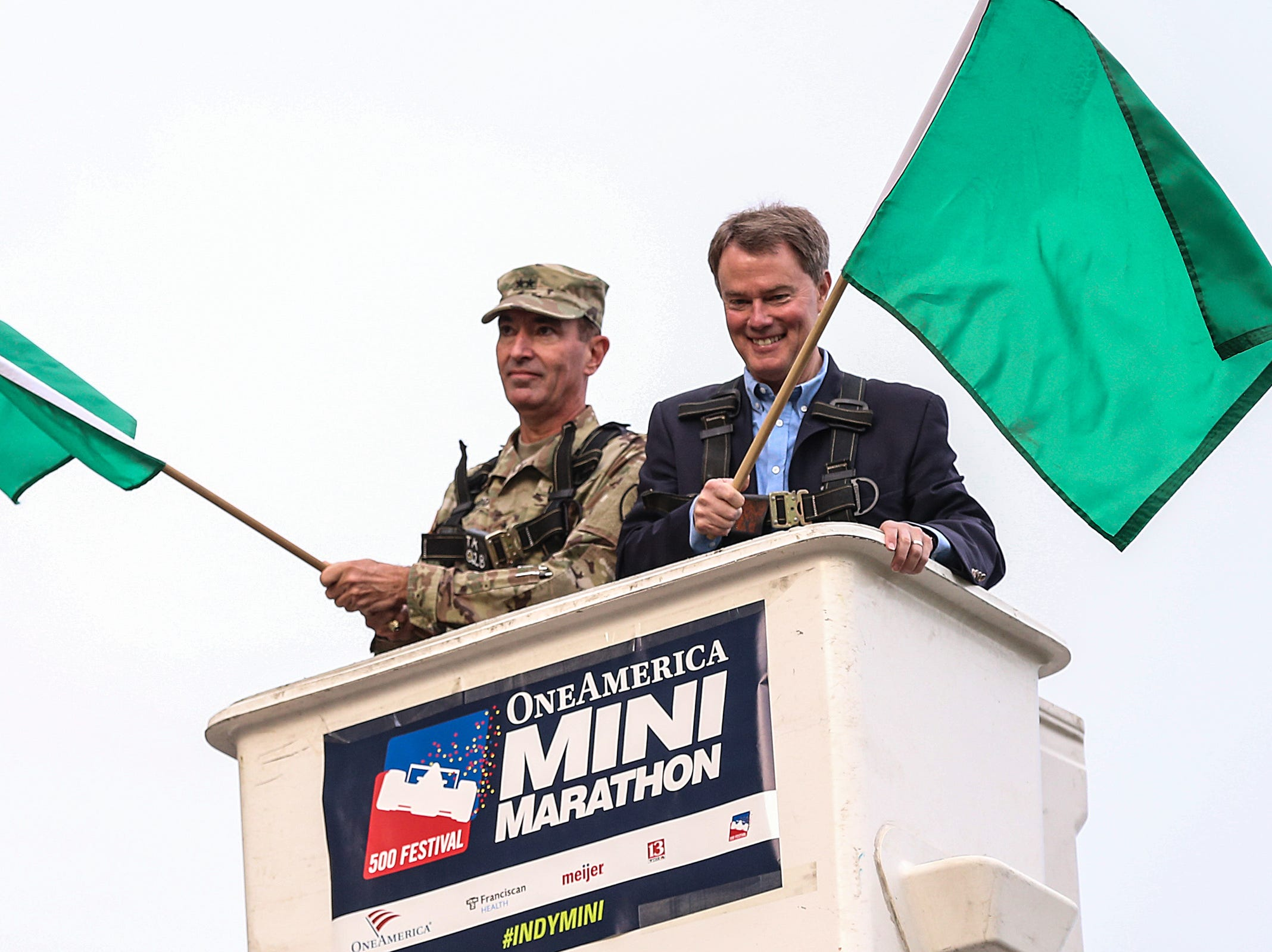 Mayor Joe Hogsett, right, waves a green flag above the starting line at the OneAmerica 500 Festival Mini-Marathon in Indianapolis, Saturday, May 5, 2018.