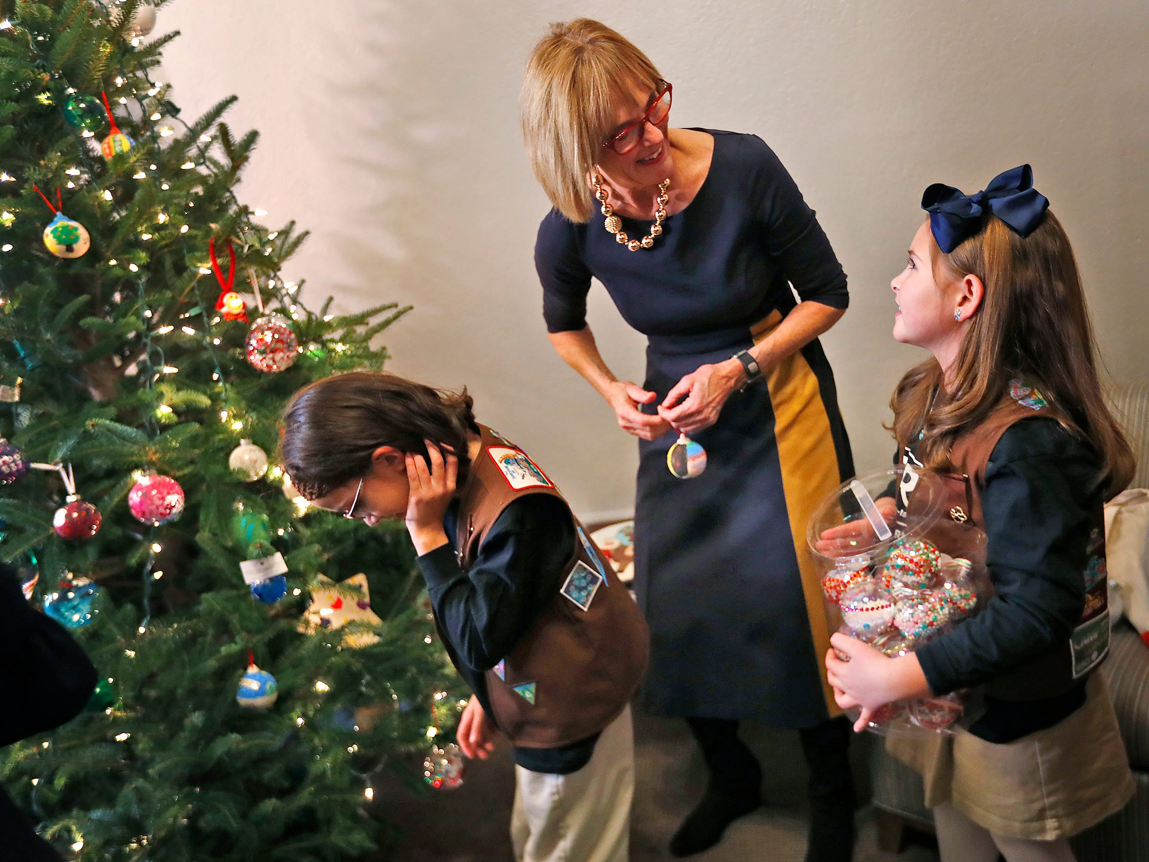 Katie Callahan, right, talks with Lieutenant Governor Suzanne Crouch, center, as they and other Brownies decorate Crouch's Statehouse tree for the holidays, Wednesday, Dec. 5, 2018.  They used ornaments created by Girl Scouts from across Central Indiana for the tree.