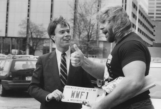 """Secretary of State Joe Hogsett and WWF wrestler Jim """"Hacksaw"""" Dugan show off limited edition license plates to be used by vehicles involved in Wrestlemania VIII in 1992."""
