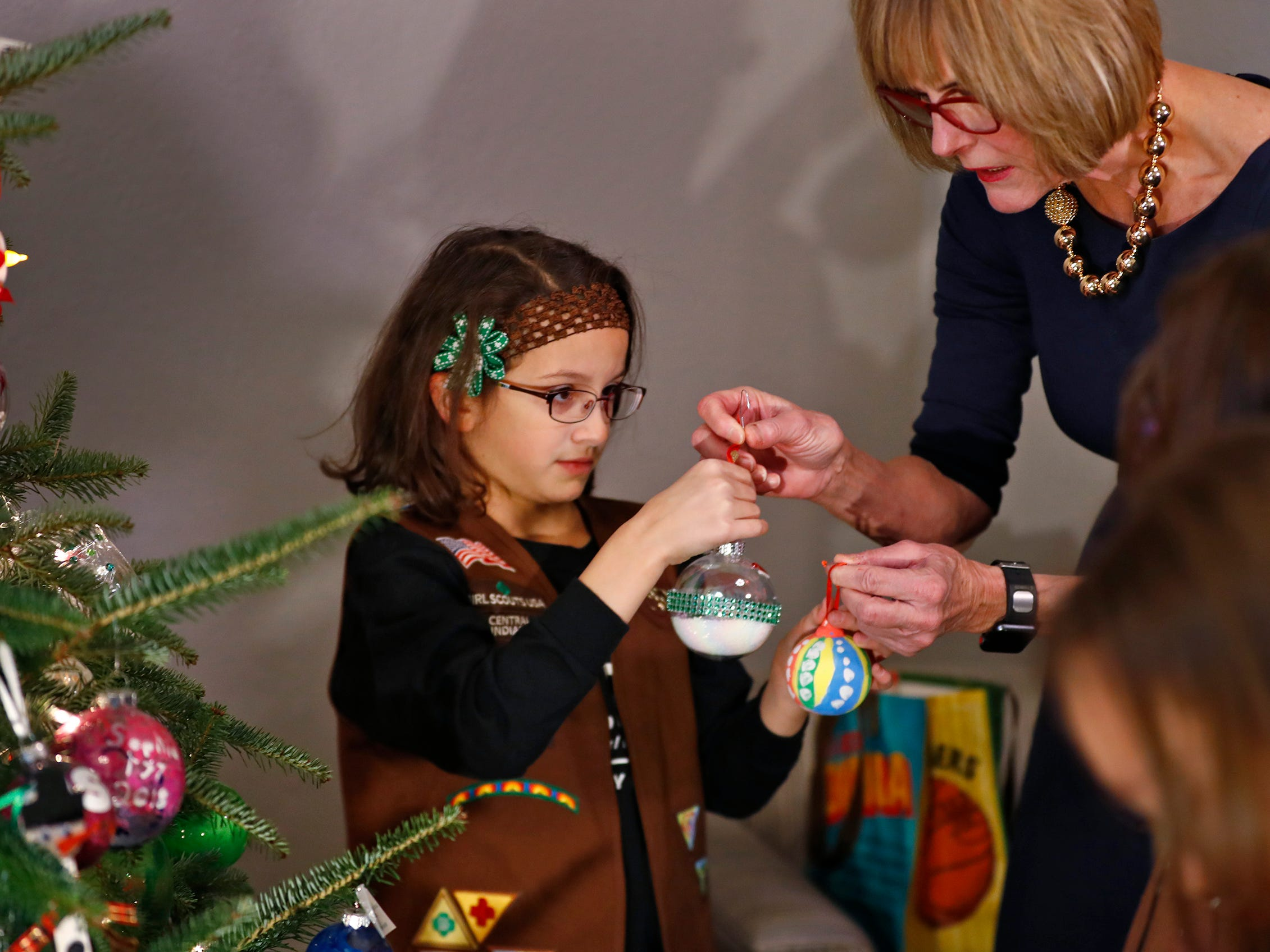Ivy Lara, left, and other Brownies join Lieutenant Governor Suzanne Crouch, right, to decorate her Indiana Statehouse tree for the holidays, Wednesday, Dec. 5, 2018.  They used ornaments created by Girl Scouts from across Central Indiana for the tree.