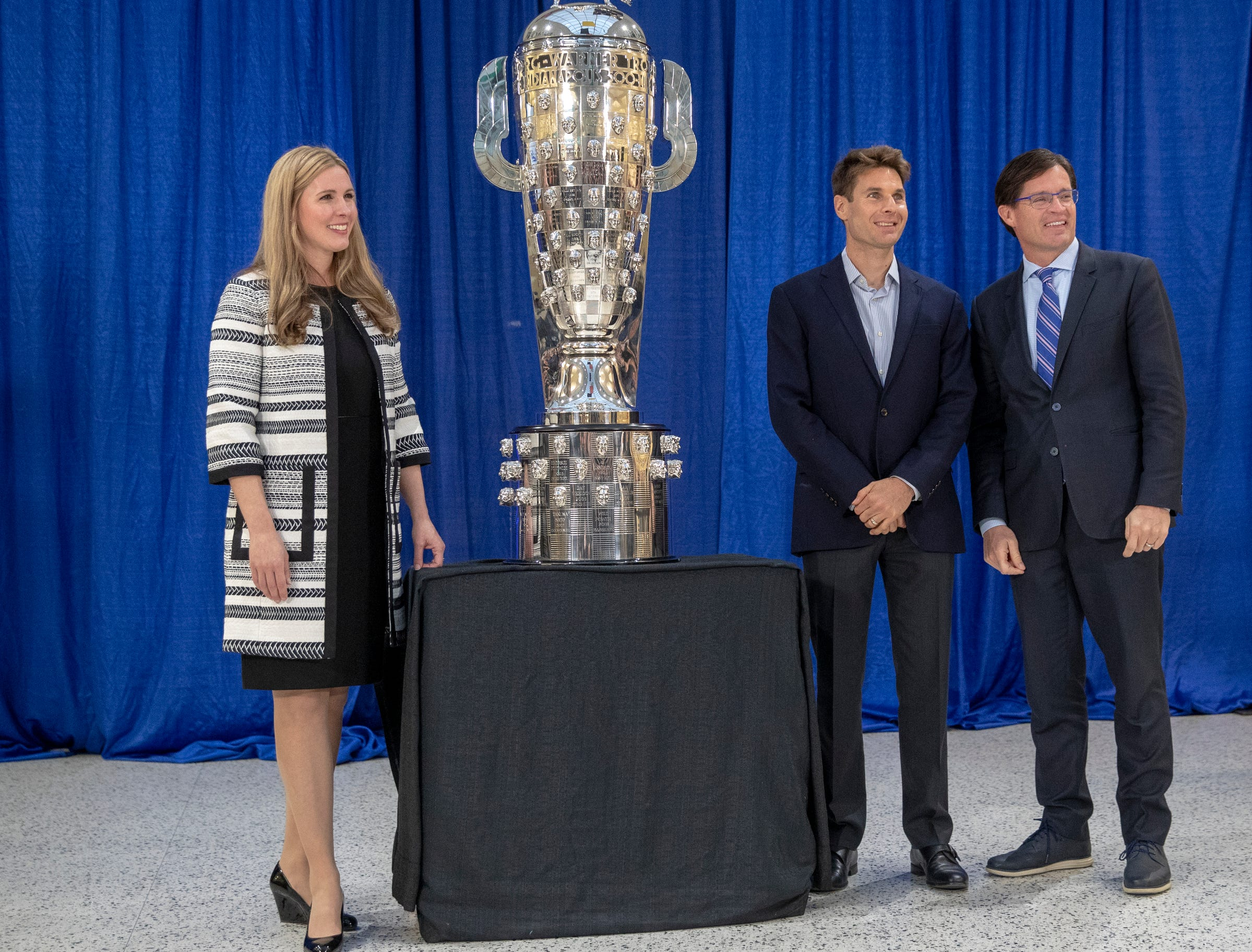 Michelle Collins (left), Will Power, and Doug Boles, pose for photos with the recently modified Borg-Warner trophy, Indianapolis Motor Speedway, Wednesday, Dec. 5, 2018. Power is an Australian driver with Team Penske, and is the 105th face on the trophy.