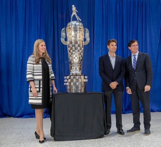 Michelle Collins (from left), 2018 Indy 500 winner Will Power and Indianapolis Motor Speedway boss Doug Boles with the recently modified Borg-Warner trophy.