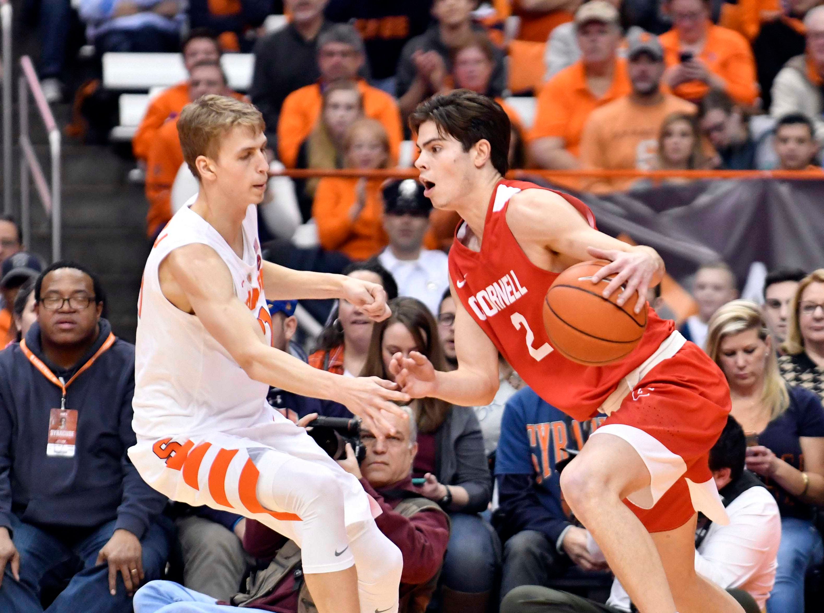 Dec 1, 2018; Syracuse, NY, USA; Cornell Big Red guard Jake Kuhn (2) drives the ball as Syracuse Orange forward Marek Dolezaj (21) defends during the second half at the Carrier Dome. Mandatory Credit: Mark Konezny-USA TODAY Sports