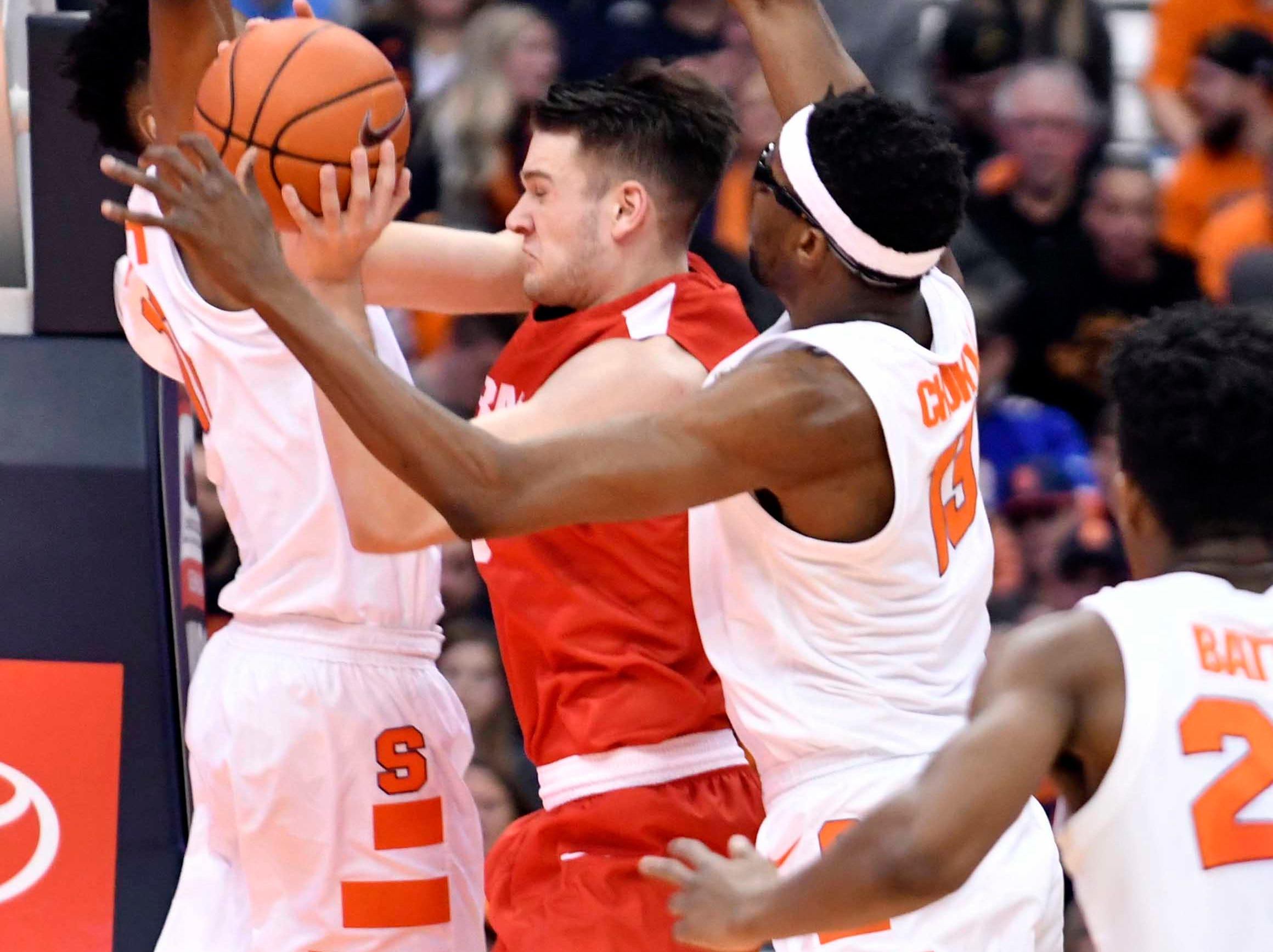 Dec 1, 2018; Syracuse, NY, USA; Cornell Big Red forward Jimmy Boeheim is squeezed between Syracuse Orange forward Oshae Brissett (11) and center Paschal Chukwu (13) on a shot during the second half at the Carrier Dome. Mandatory Credit: Mark Konezny-USA TODAY Sports