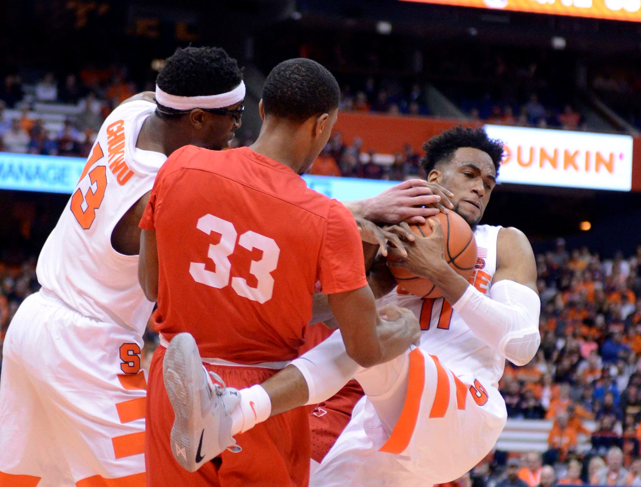 Dec 1, 2018; Syracuse, NY, USA; Syracuse Orange forward Oshae Brissett (11) grabs a rebound over Cornell Big Red forward Steven Julian (33) during the second half at the Carrier Dome. Mandatory Credit: Mark Konezny-USA TODAY Sports