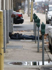 In this file photo, a man lies on a sidewalk in downtown Jackson during cold weather.