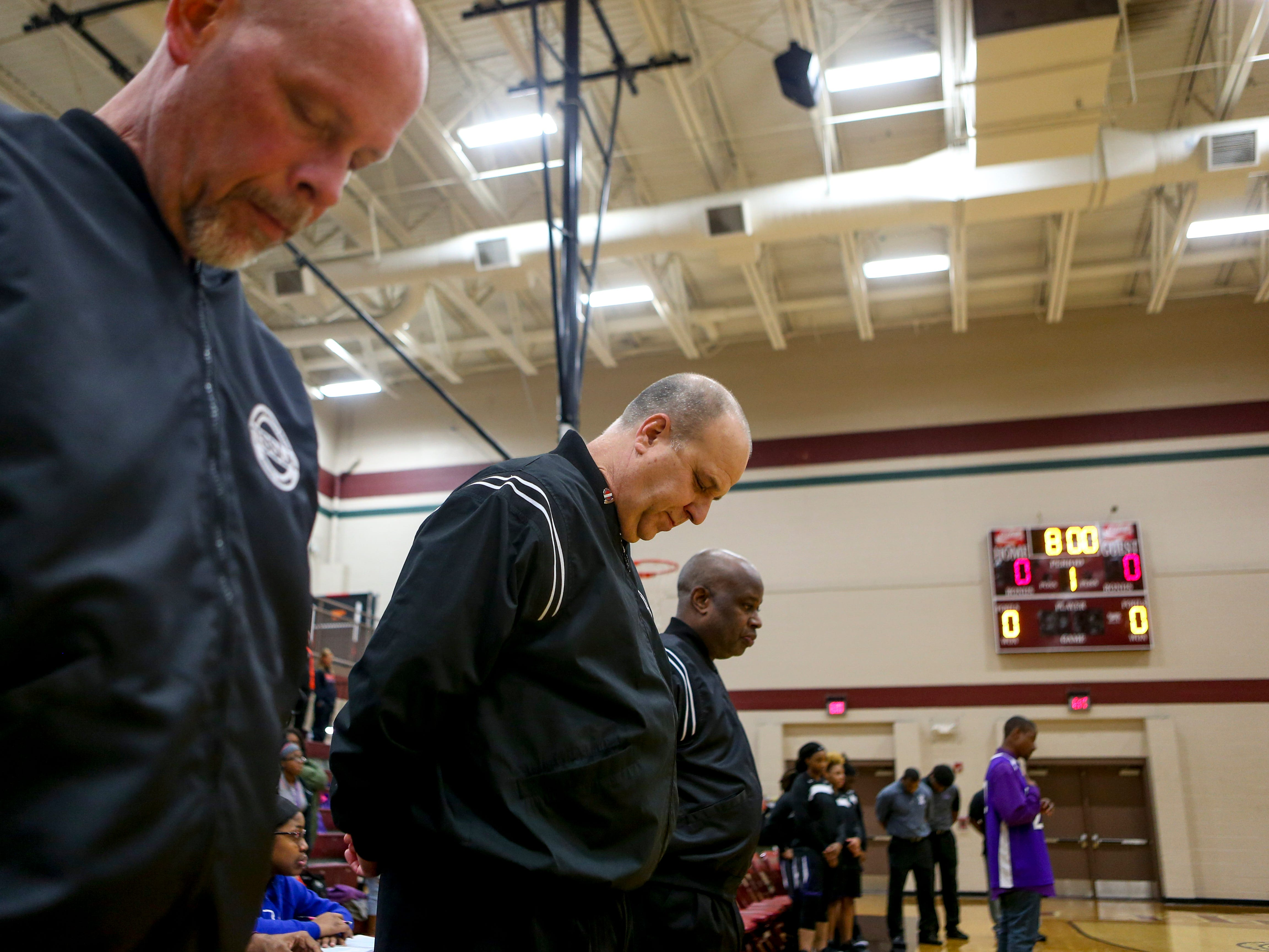 Referees bow their heads during a moment of silence held for Nyema and Nyjah Jackson at a TSSAA girls basketball game where Liberty played Ripley High School at Liberty Tech High School in Jackson, Tenn., on Tuesday, Dec. 4, 2018.