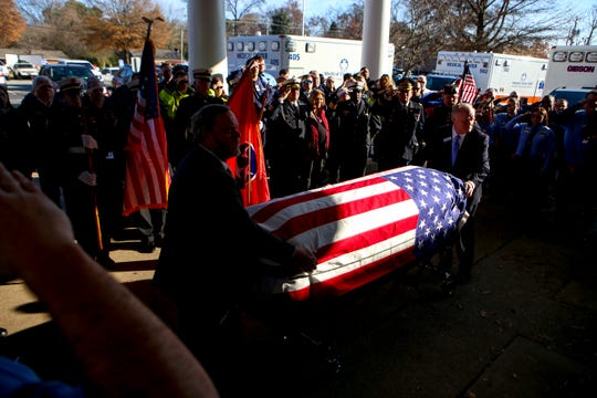 Attendees, family members, and fellow first responders salute and pay their last respects as the body of Zach Pruitt is placed into an ambulance before the procession headed to Englewood Baptist Church in Jackson, Tenn., on Wednesday, Dec. 5, 2018.
