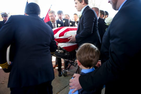 Rylan Pruitt, foreground, watches as the body of his father Zach Pruitt is hoisted into an ambulance by family members and friends at Englewood Baptist Church in Jackson, Tenn., on Wednesday, Dec. 5, 2018.
