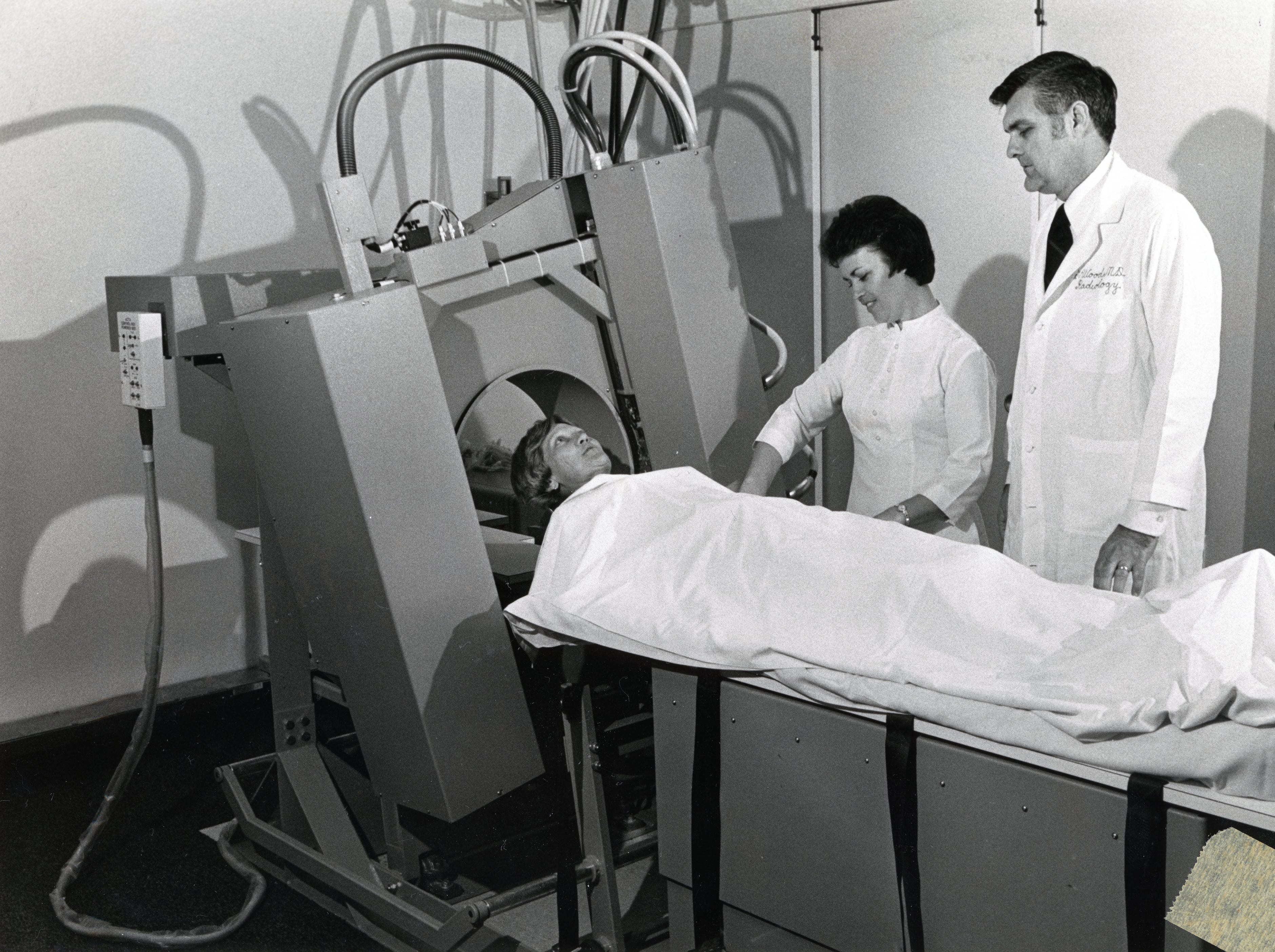 Joyce Norman, work coordinator, is used as a model on the whole body scanner at St. Mary's Medical Center in April 1976. Technologist Nellie Thomas and Dr. George Woods watch.