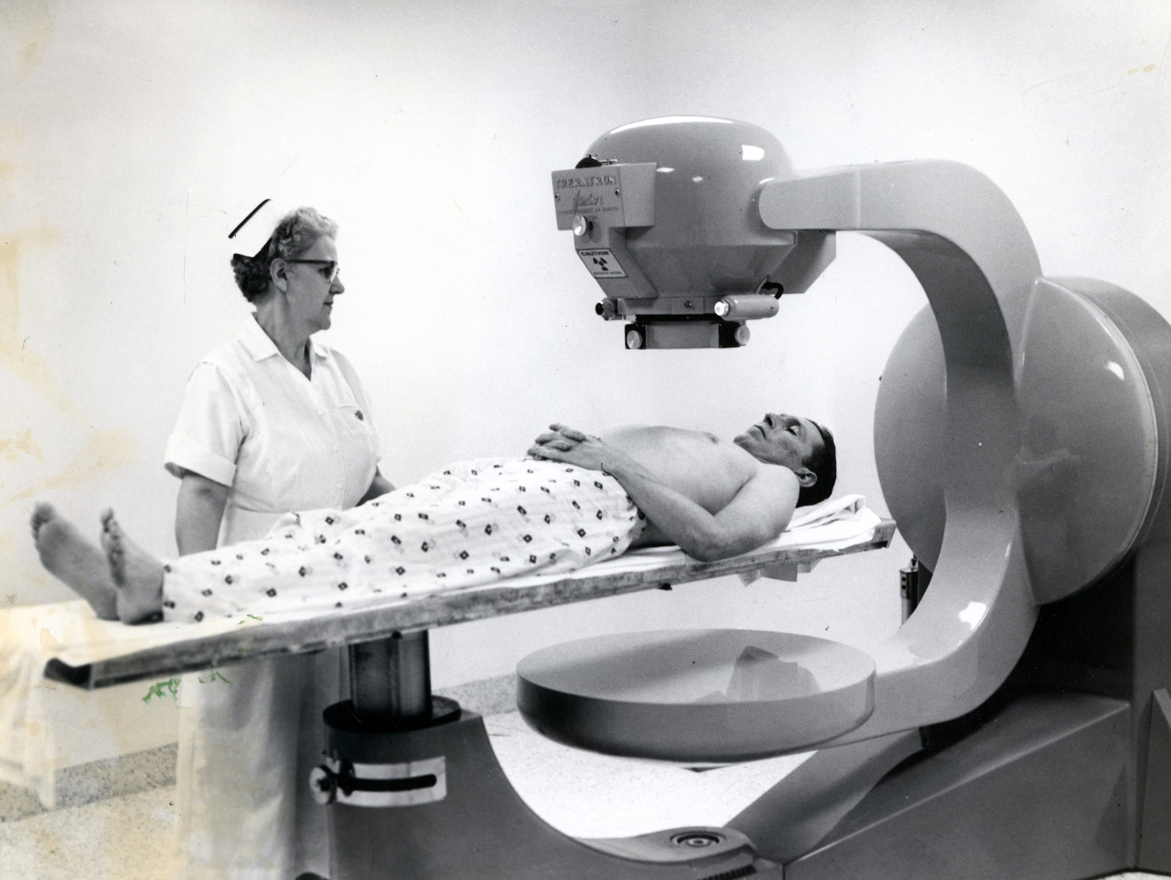 Nurse Grace Jett prepares patient John E. Myers for an x-ray treatment at St. Mary's Hospital in May 1958. Myers is the first patient to get treatment, and in the actual treatment, there would be no one in the room with the patient.
