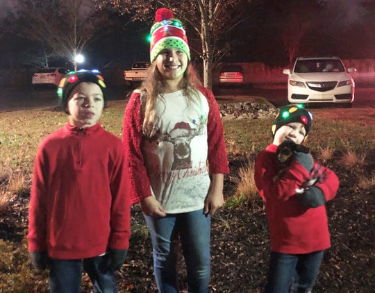 "Will Holbert with siblings Kelsey and Wade, and Clark the basset hound, at the Halls Christmas Tree lighting in Clayton Park on Dec. 1. ""I love that we have a place we can come to,"" said their mom, Shelli Holbert. ""A place we can come to and have these kinds of activities."""