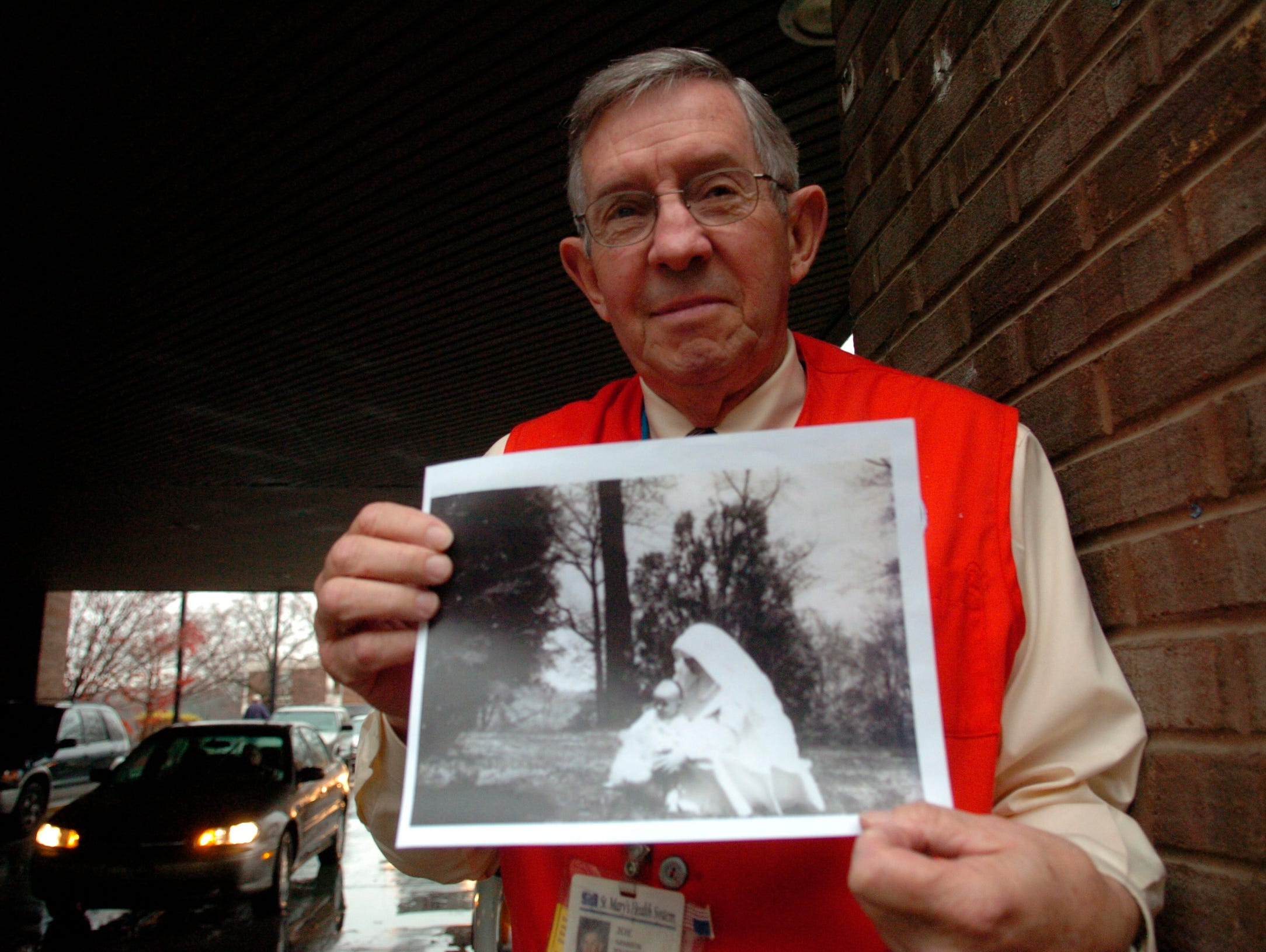 Joe Hannifin, right, President of St. Mary's auxillary volunteers, holds a photo of himself as a baby being held by a nun at St. Mary's Hospital while standing at the main entrance outside of the hospital Thursday afternoon in North Knoxville. Hannifin was a baby raised at St. Mary's Hospital.--12/09/2004