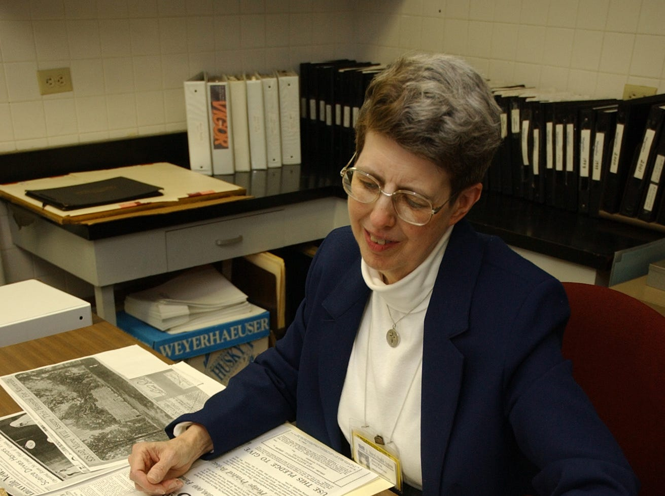 Sister Mary Martha Naber compiles archival images Wednesday for a coffee-table book on the history of St. Mary's Medical Center. 12/1/04.