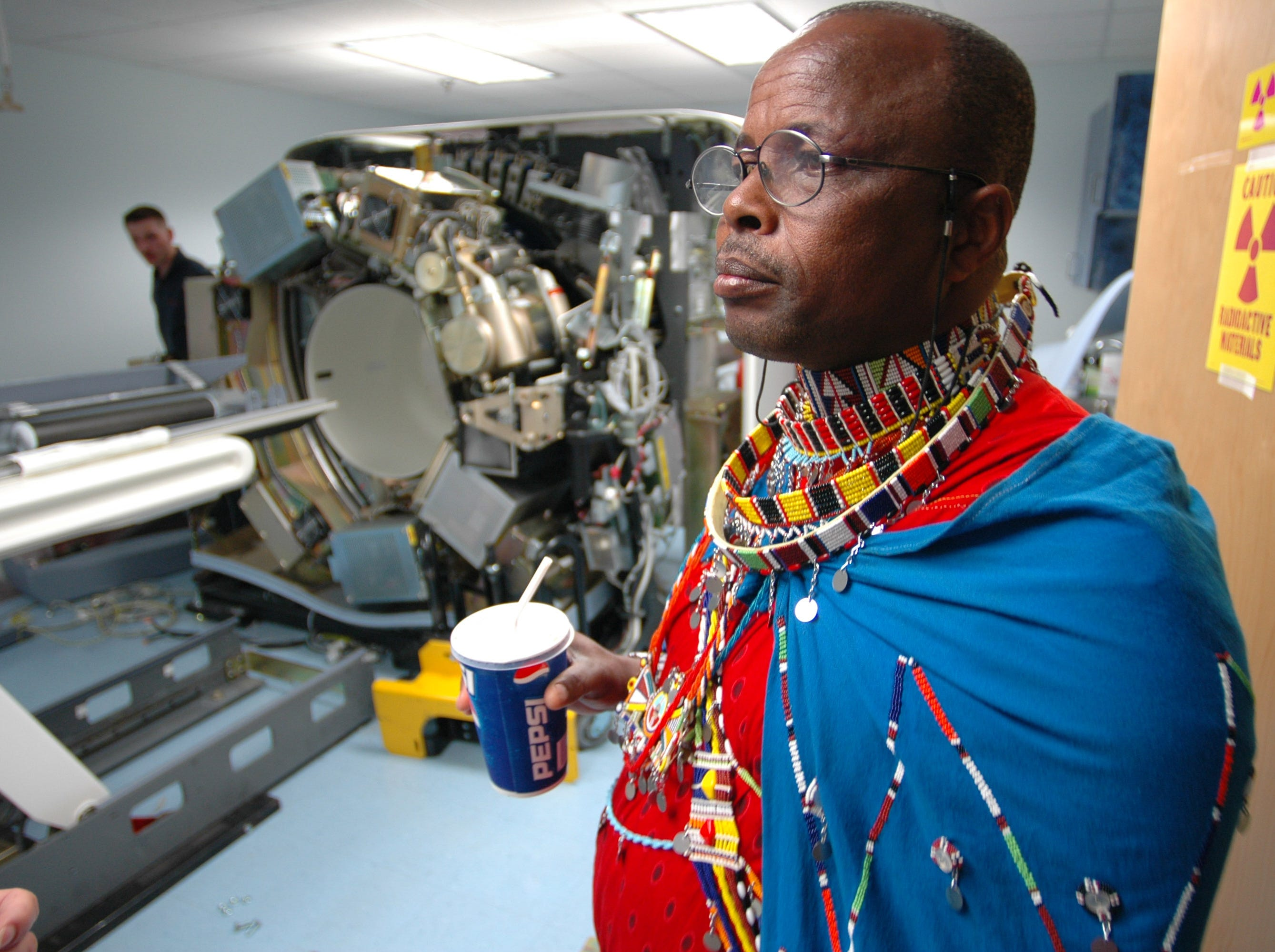 Dressed in his traditional clothing, Josiah Muesha, a member of the Maasai community in Kenya, checks out a PET scan machine which is being serviced while drinking a pepsi on his tour of St. Mary's Hospital in North Knoxville Tuesday afternoon. Many of the colors that he wears are symbolic, including the band across his chest which signifies that he is a Maasai warrior. To become a warrior, one must go into the wilderness alone with a sword and a knife and not come back until they have killed a lion.0/18/2005