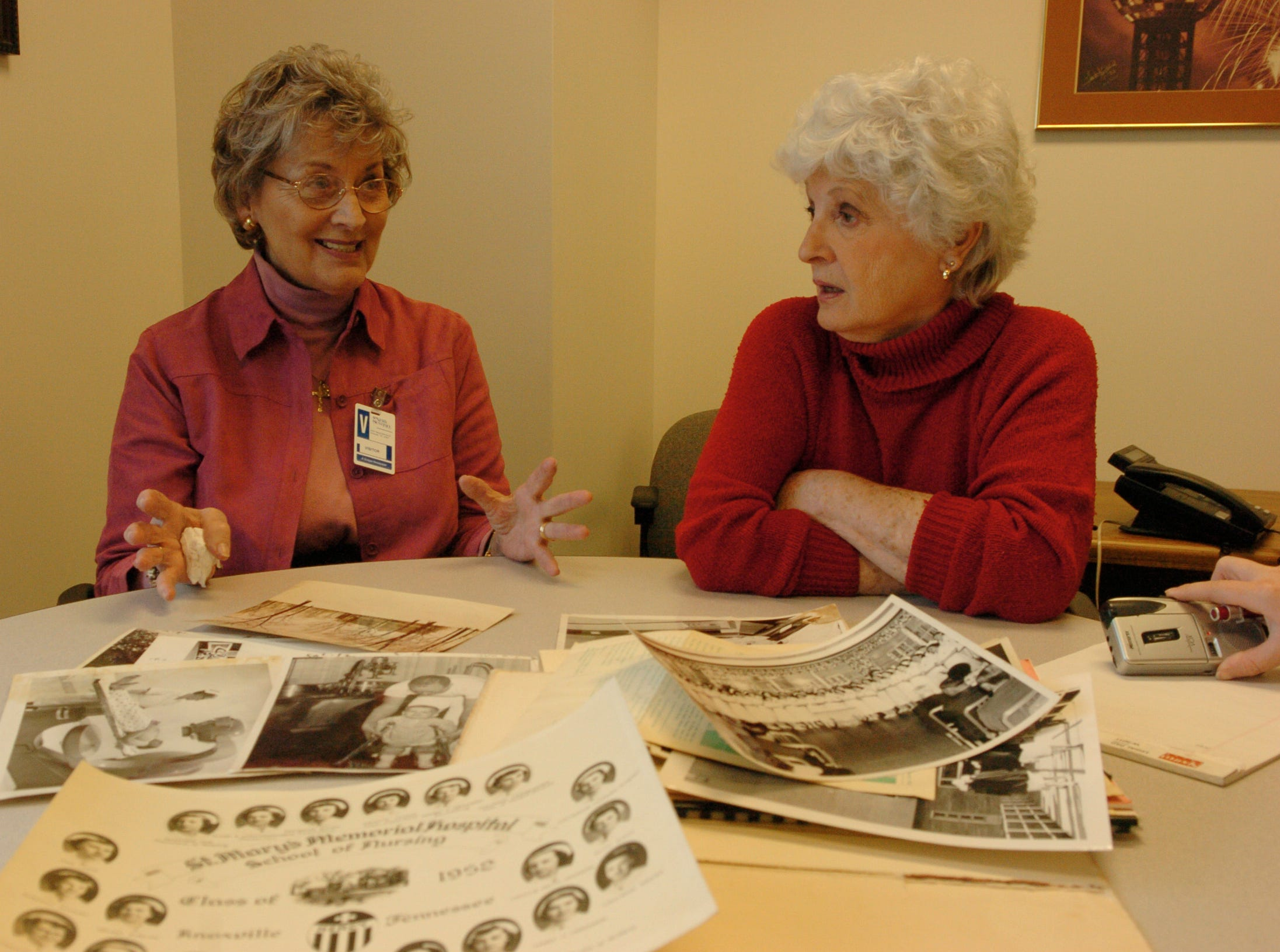 Frankie Hood (left ) Nancy Stephens look over photos from when they were in nursing school over 50 years ago.  Frankie Hood and Nancy Stephens graduated from St. Mary's nursing school in 1952.   Both women are still friends with each other and others in the class.