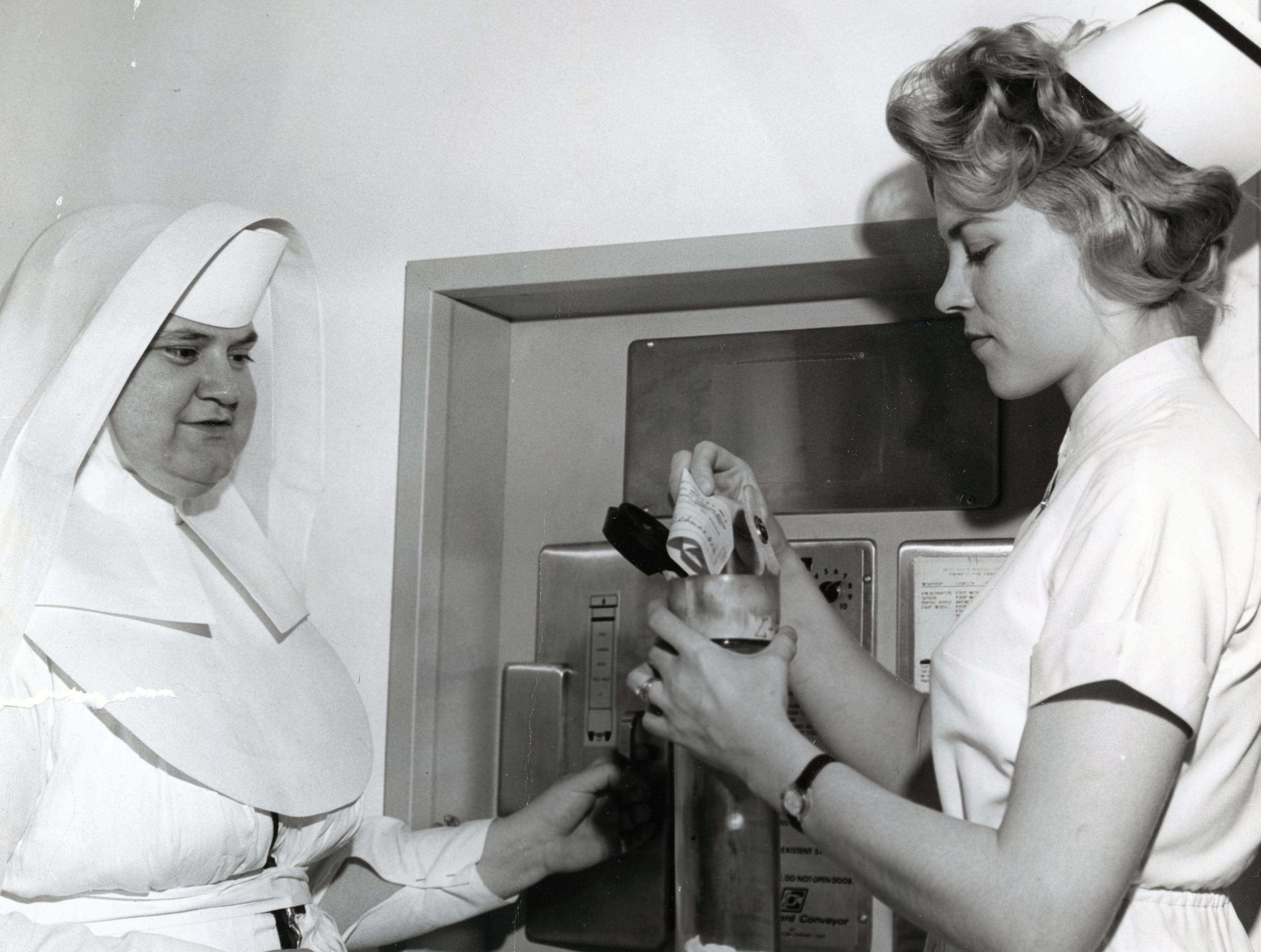 Sister Mary Laura, administrator at St. Mary's, and Barbara Coleman, registered nurse and instructor, with a pneumatic tube system at St. Mary's Hospital in March 1965.