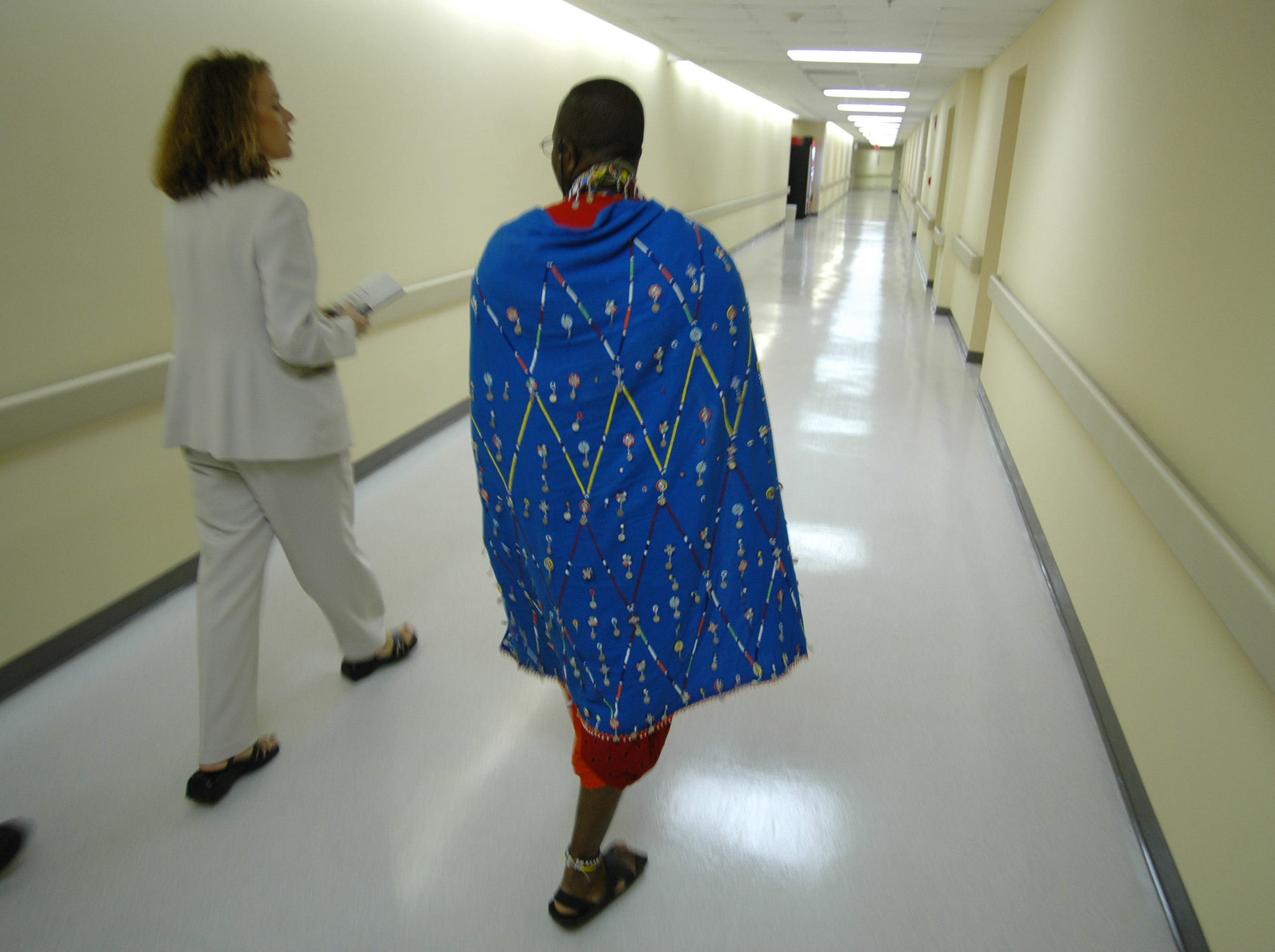 Dressed in his traditional clothing, Josiah Muesha, a member of the Maasai community in Kenya, right, walks with Linda Cox-Leija of St. Mary's Hospital on his tour of the hospital in North Knoxville Tuesday afternoon. 10/18/2005