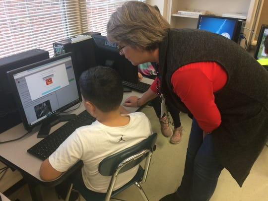 Fourth-grade teacher Barbara Enloe helps a student at the computer.