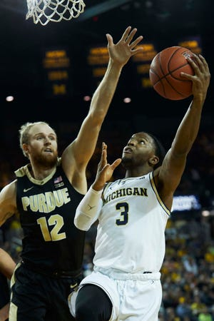 Dec 1, 2018; Ann Arbor, MI, USA; Michigan Wolverines guard Zavier Simpson (3) shoots on Purdue Boilermakers forward Evan Boudreaux (12) in the first half at Crisler Center. Mandatory Credit: Rick Osentoski-USA TODAY Sports