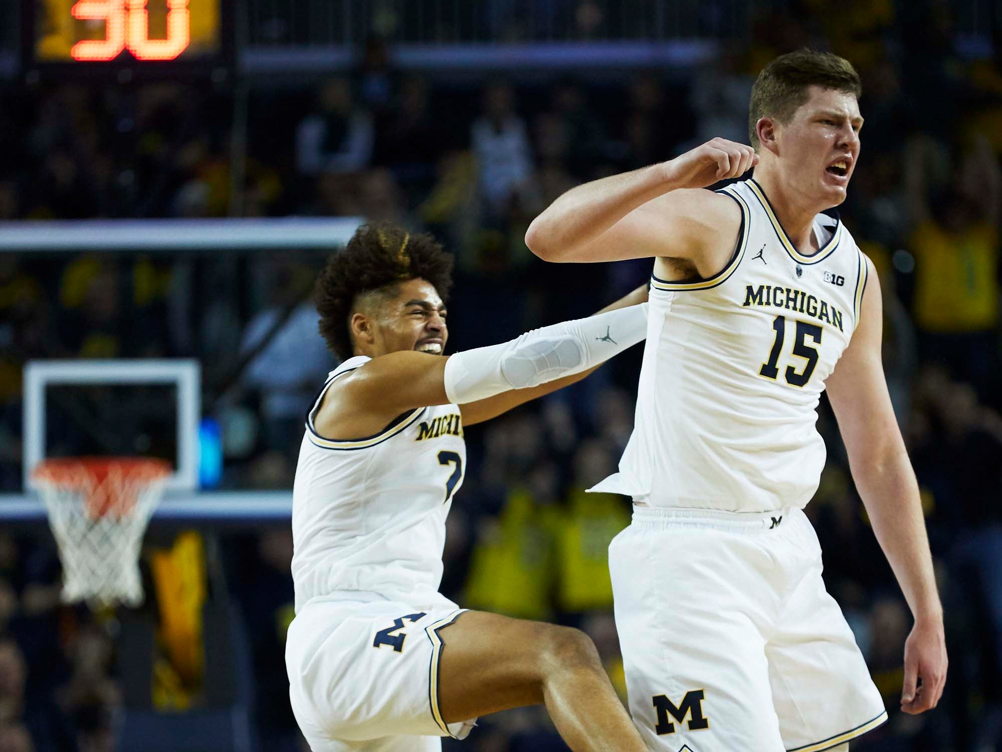 Dec 1, 2018; Ann Arbor, MI, USA; Michigan Wolverines center Jon Teske (15) and guard Jordan Poole (2) celebrate during the first half against the Purdue Boilermakers at Crisler Center. Mandatory Credit: Rick Osentoski-USA TODAY Sports