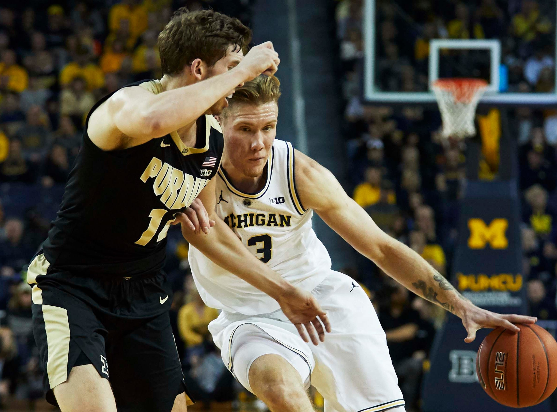 Dec 1, 2018; Ann Arbor, MI, USA; Michigan Wolverines forward Ignas Brazdeikis (13) dribbles defended by Purdue Boilermakers guard Tommy Luce (15) at Crisler Center. Mandatory Credit: Rick Osentoski-USA TODAY Sports