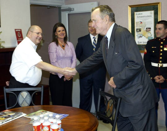 Former President George H.W. Bush arrives at Lafayette Regional Airport on Friday 4/28/06. Here he shakes hands with George Cummings. Bush is in Lafayette to speak at the Paramedic Luncheon at the Cajundome Convention center.