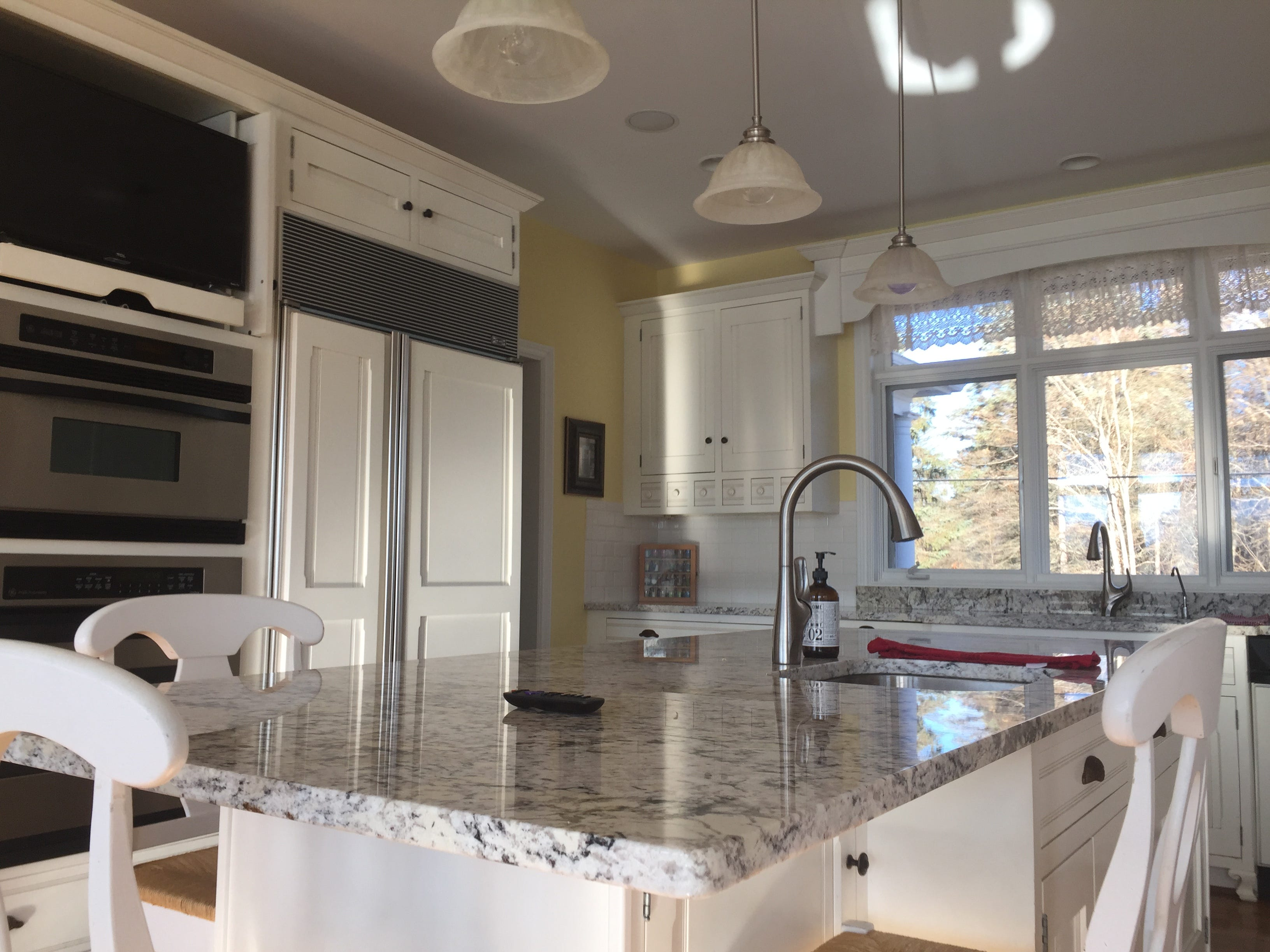 A granite kitchen island provides extra space for family dining and entertaining guests in a Clifford Road home in Genoa Township, shown Tuesday, Dec. 4, 2018