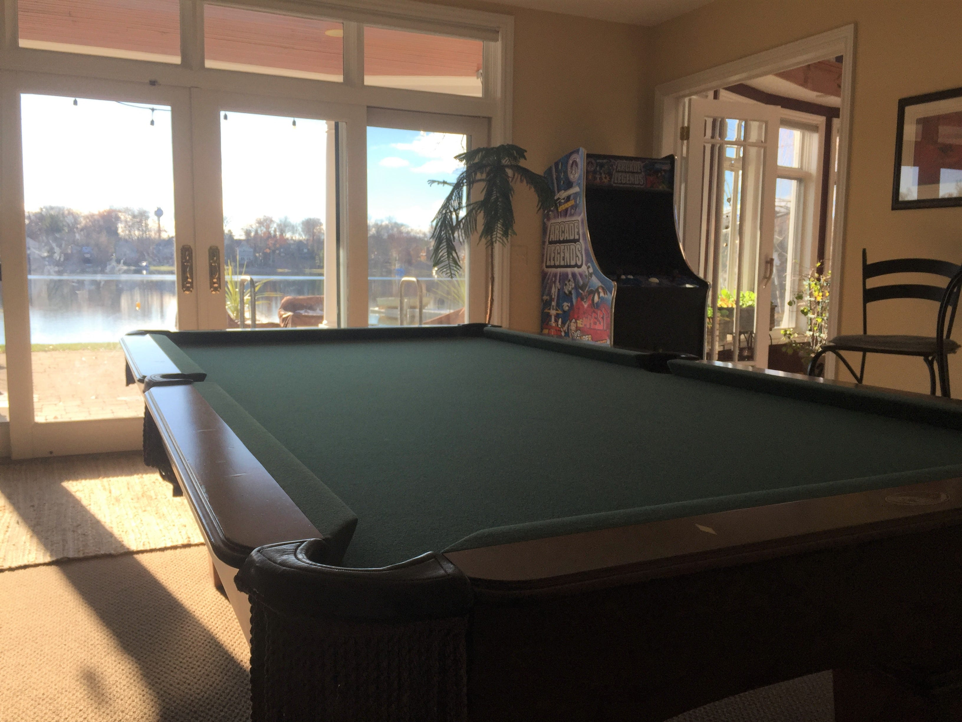 An arcade game and pool table create an entertainment space on the lower-level walk-out basement in a Clifford Road home in Genoa Township, shown Dec. 4, 2018
