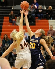 Hartland's Lillee Gustafson (20) and Fenton's Chloe Idoni (14) battle for the opening tip of the season on Tuesday, Dec. 4, 2018.