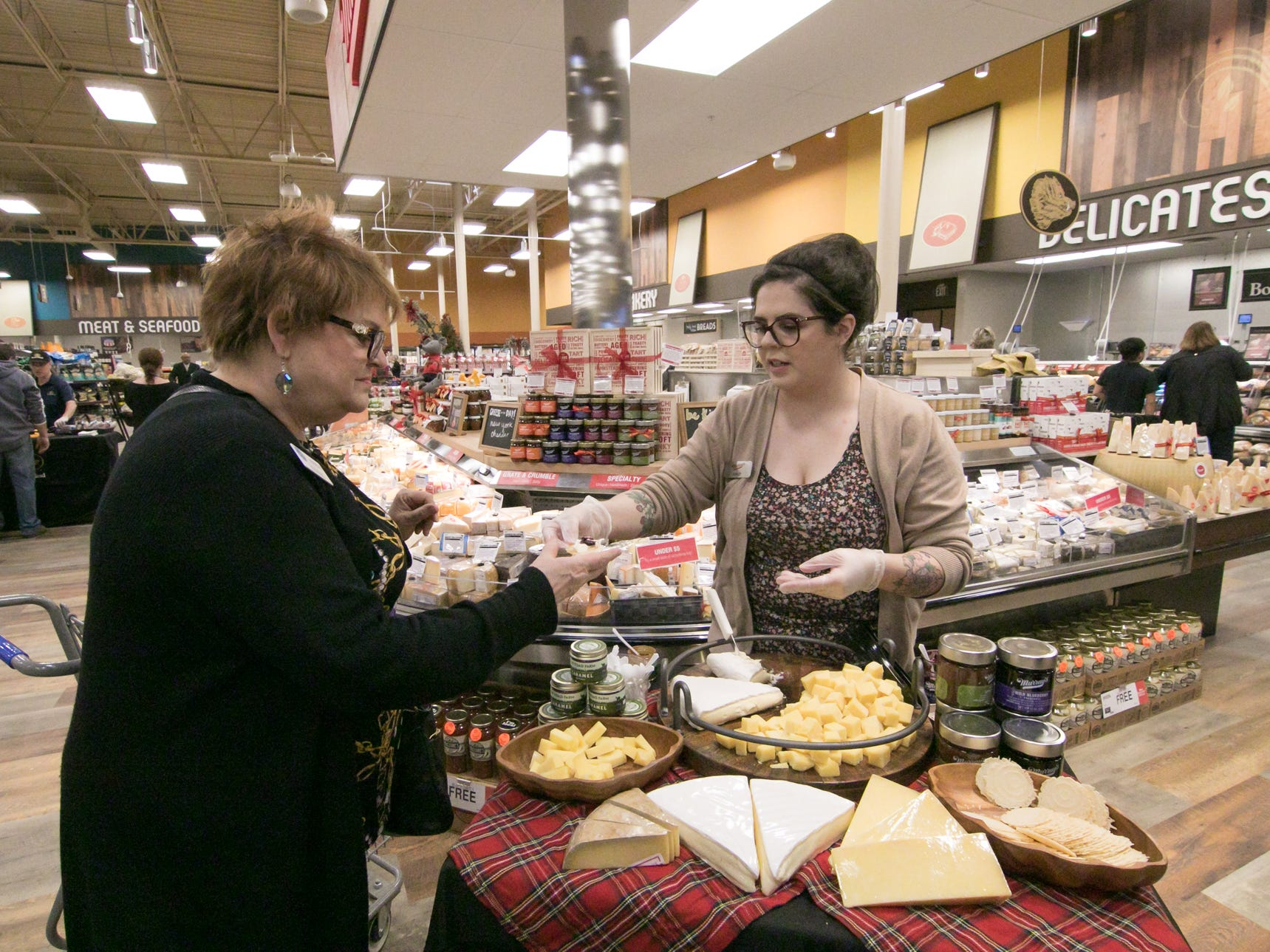 Murray's Cheese specialist Ashley Fisher, right, offers a sample to Sally Eastman, Greater Brighton Area Chamber of Commerce member director, at a ribbon cutting celebration of the expanded store, Wednesday, Dec. 5, 2018.