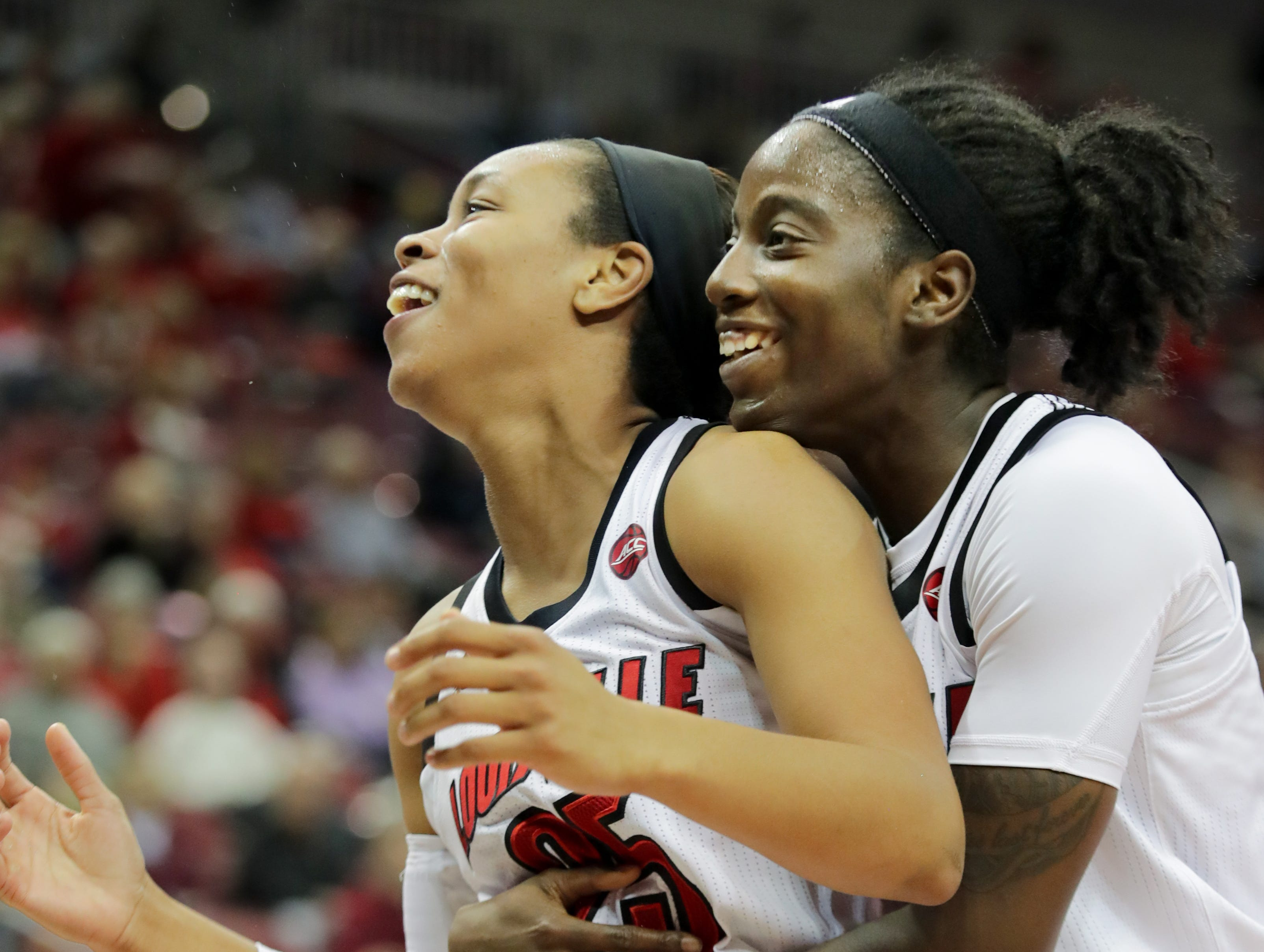 Louisville's Asia Durr, left, and Jazmine Jones share a moment after Durr misses a shot.  