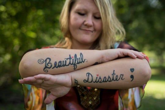 Austin, Indiana resident Sabina Adams shows her forearm tattoos. Aug. 22, 2018