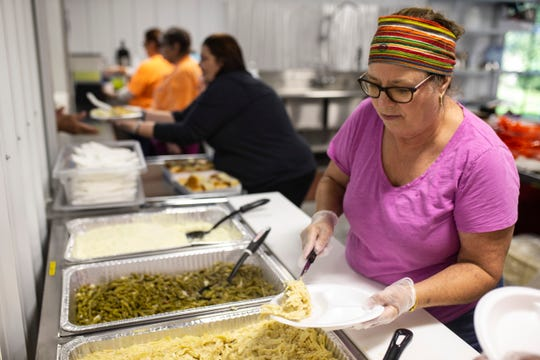 Becky Thomas fills up plates of food for those in need during the weekly Thursday night feeding event held at the Church of the New Covenant on Rural Street in Austin, Indiana. Oct. 18, 2018